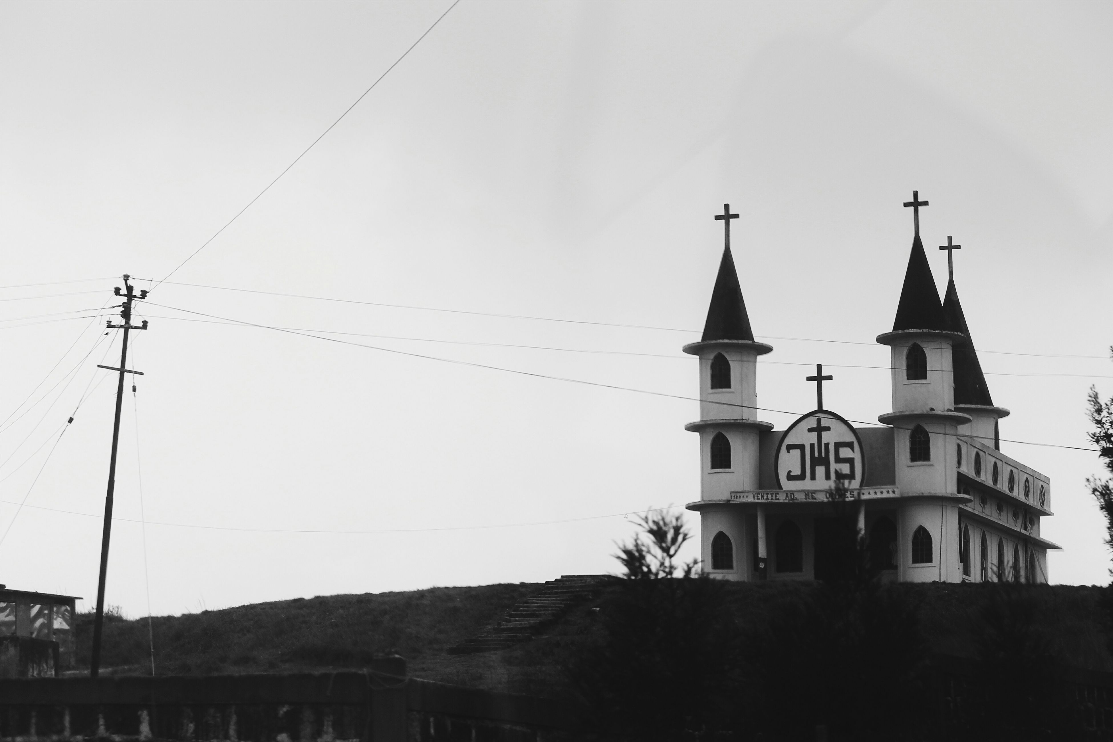 building exterior, architecture, built structure, church, low angle view, religion, place of worship, spirituality, cross, sky, clear sky, high section, house, power line, outdoors, day, fuel and power generation, no people