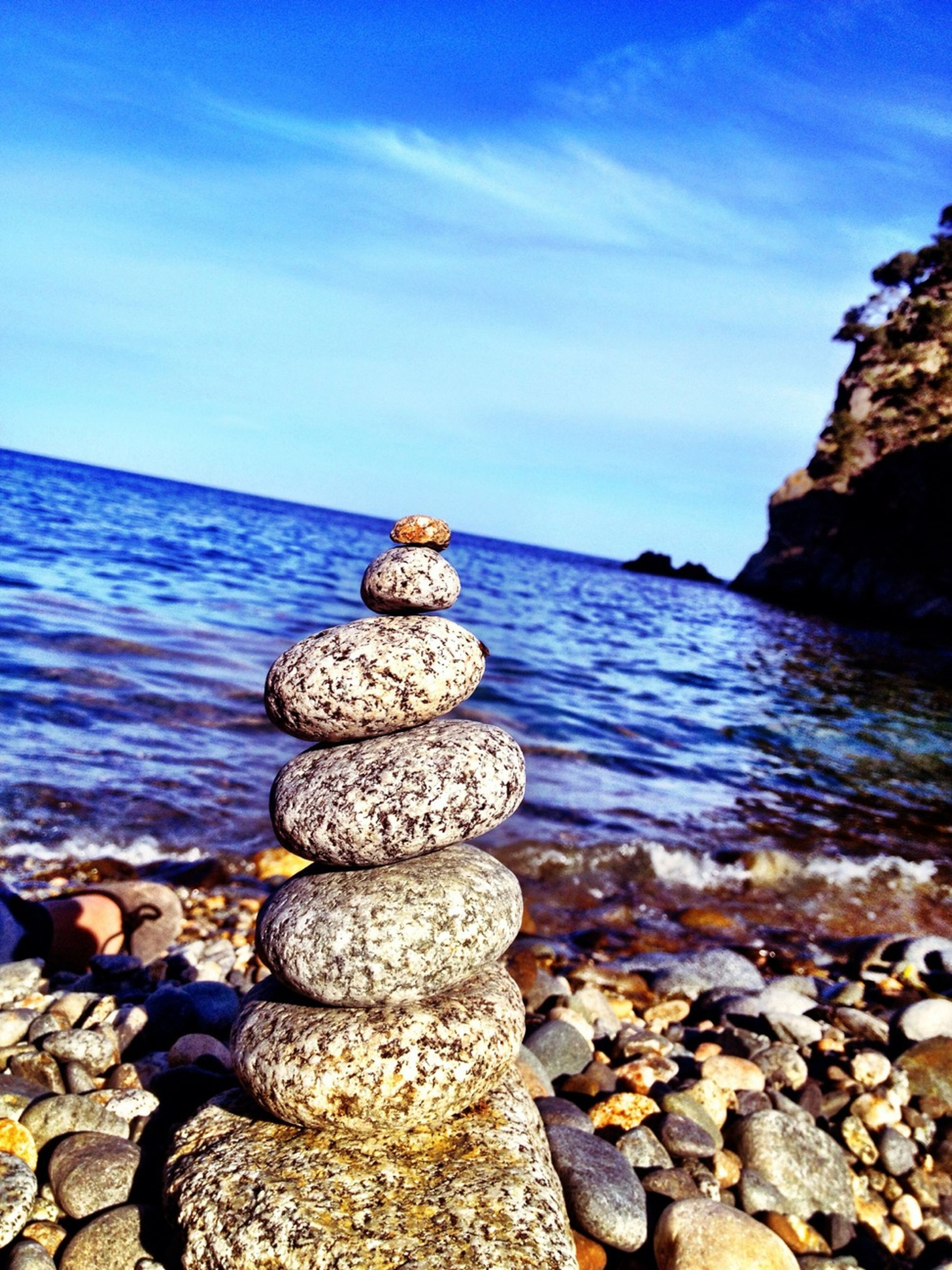 sea, water, rock - object, stone - object, pebble, horizon over water, blue, sky, tranquility, beach, tranquil scene, scenics, beauty in nature, shore, stone, nature, rock, stack, idyllic, cloud - sky
