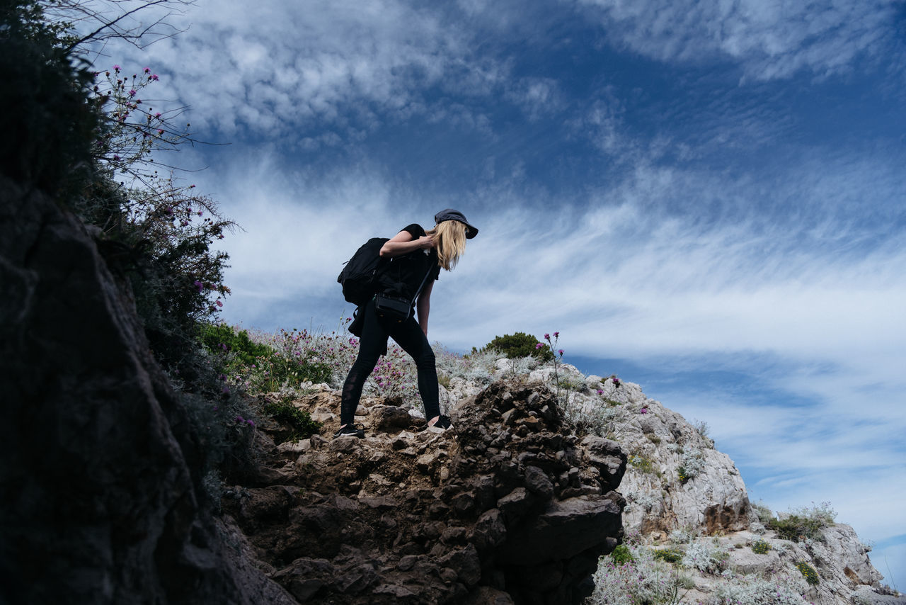 rock - object, full length, cloud - sky, sky, adventure, real people, nature, outdoors, men, backpack, day, standing, one person, low angle view, mountain, leisure activity, lifestyles, scenics, beauty in nature, landscape, camera - photographic equipment, extreme sports, young adult, people