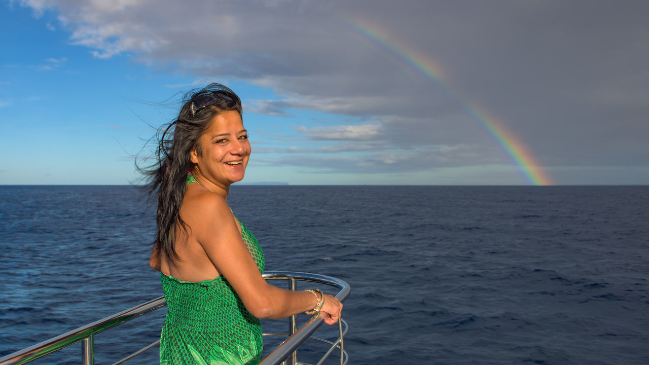 Smiles and rainbows of the Kauai coast Adults Only Carefree Cheerful Cloud - Sky Copy Space Freedom Fun Green Dress Happiness Horizon Over Water Ocean One Person Only Women Outdoors Pacific Rainbow Sailing Ship Sky Smiling Sunny Travel Travel Destinations Vacations Woman