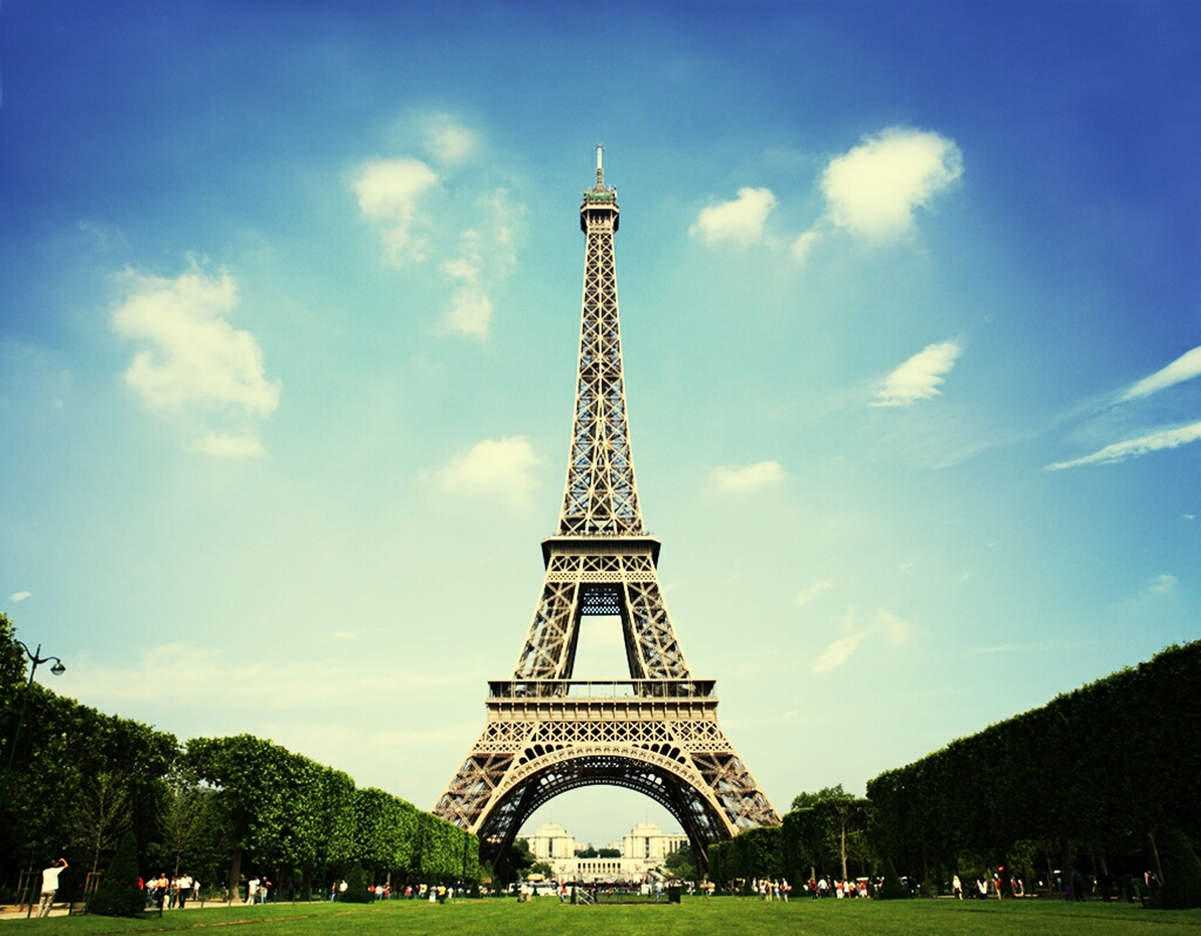 architecture, famous place, sky, built structure, eiffel tower, international landmark, travel destinations, tourism, tower, capital cities, travel, history, culture, tree, large group of people, cloud - sky, grass, tall - high, metal