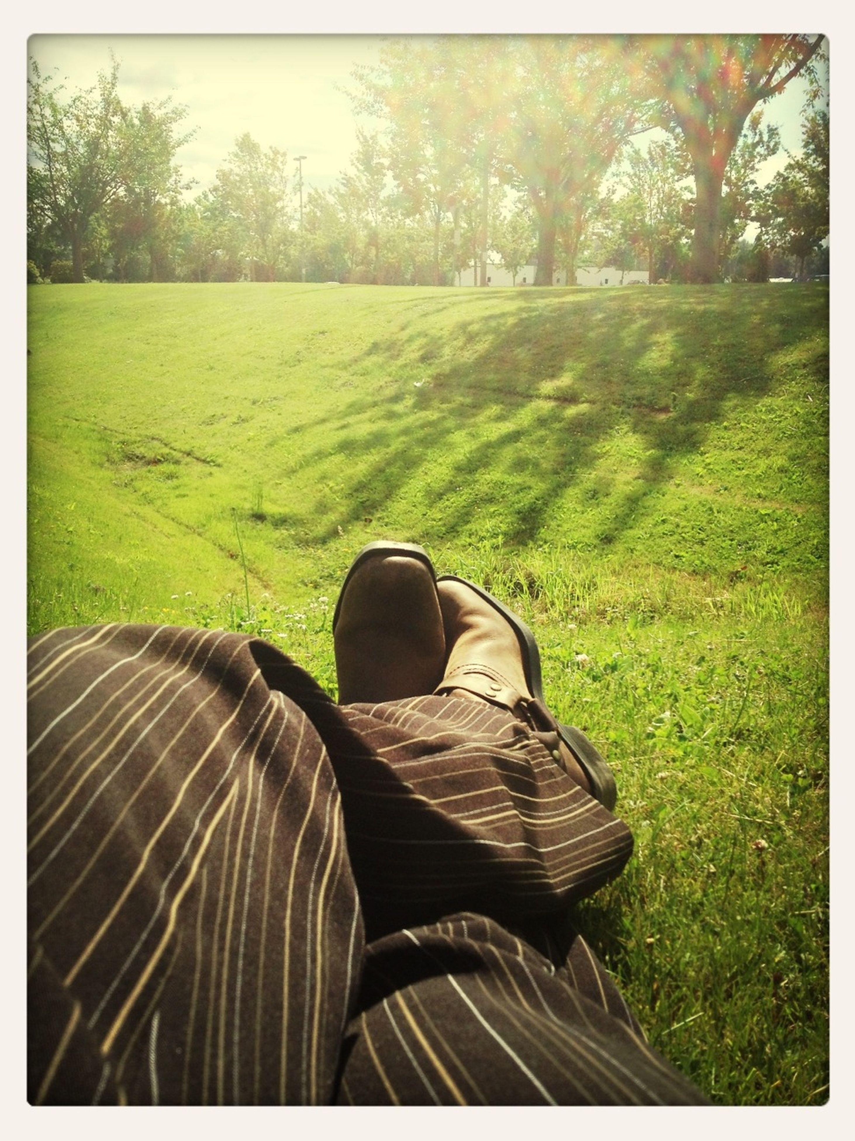 grass, low section, shoe, field, transfer print, person, auto post production filter, grassy, green color, lifestyles, leisure activity, footwear, landscape, tranquility, men, nature, tree, outdoors