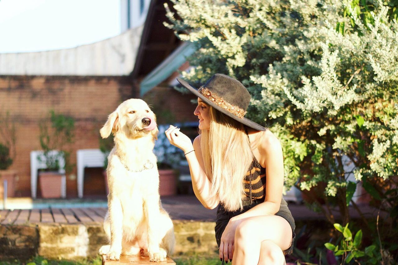 dog, pets, one animal, animal themes, real people, outdoors, domestic animals, building exterior, day, leisure activity, mammal, casual clothing, lifestyles, sunlight, happiness, full length, friendship, smiling, young women, bonding, young adult, nature, tree, people