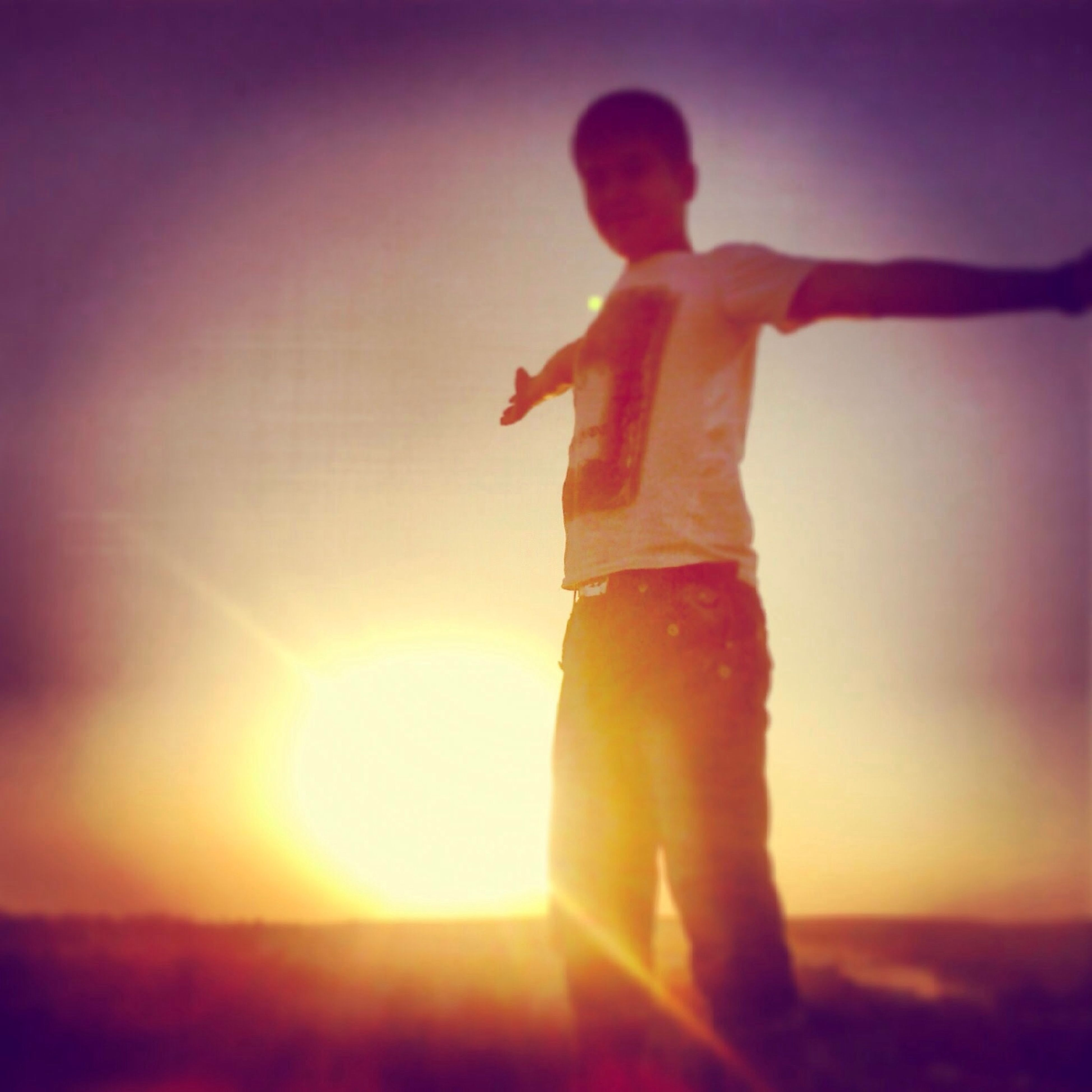sun, sunset, lifestyles, sunlight, lens flare, leisure activity, sunbeam, sky, standing, orange color, arms raised, silhouette, side view, full length, auto post production filter, vignette, arms outstretched, low angle view