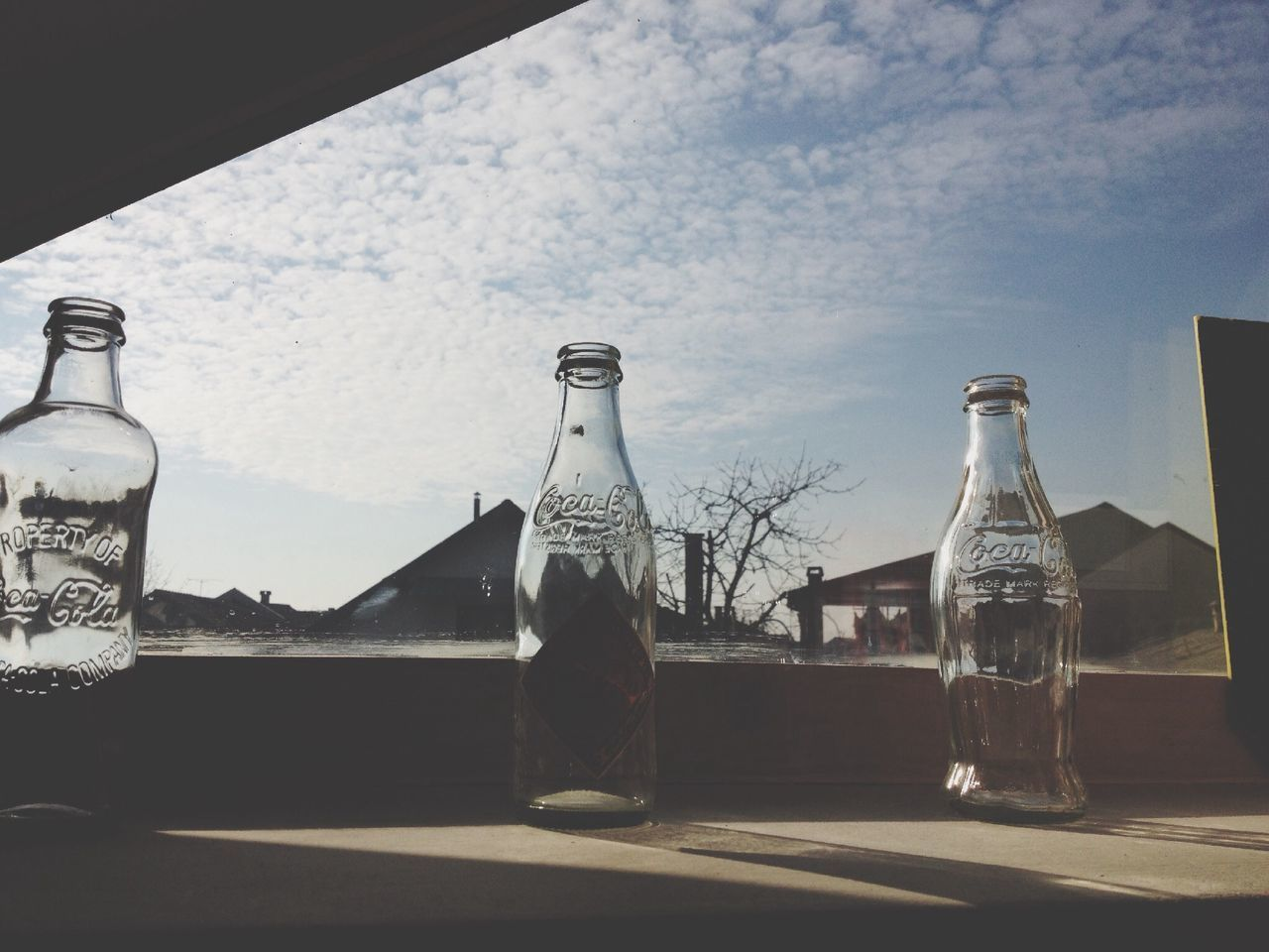 glass - material, bottle, table, drinking glass, sky, no people, drink, water, day, window, indoors, architecture, nature, close-up