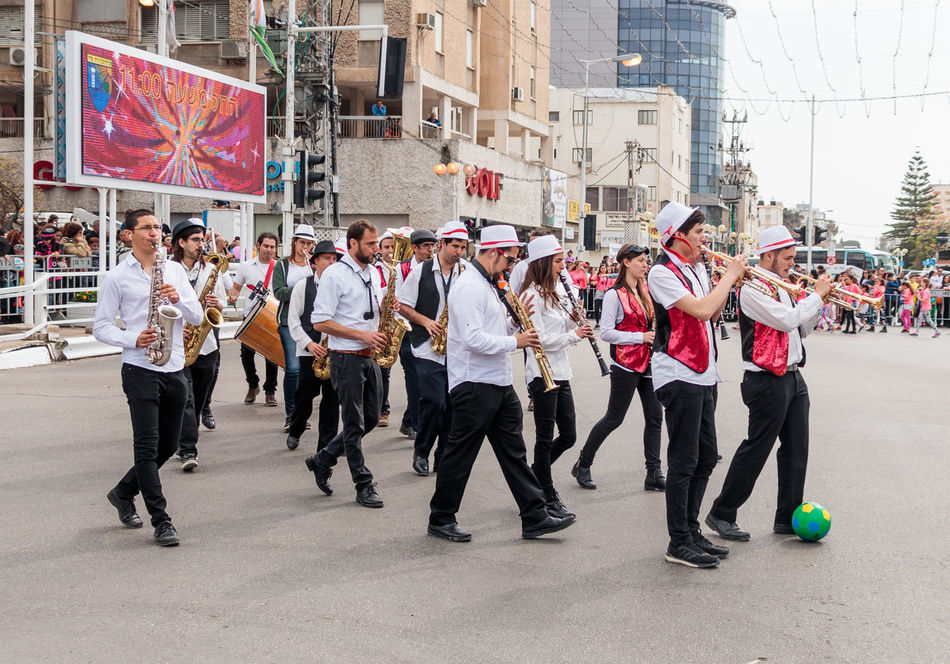 """Nahariyya, Israel, March 10, 2017 : Participantin in the traditional annual carnival parade """"Adloyada"""" walking near the viewers and playing on wind musical instruments in Nahariyya, Israel Adloyada Adult Beauty Carnival Celebration Colorful Costume Culture Day Decoration Dressed Entertainment Festival Fun Happy Israel Masquerade Nahariyya Outdoors Parade Party People Style Traditional Travel"""