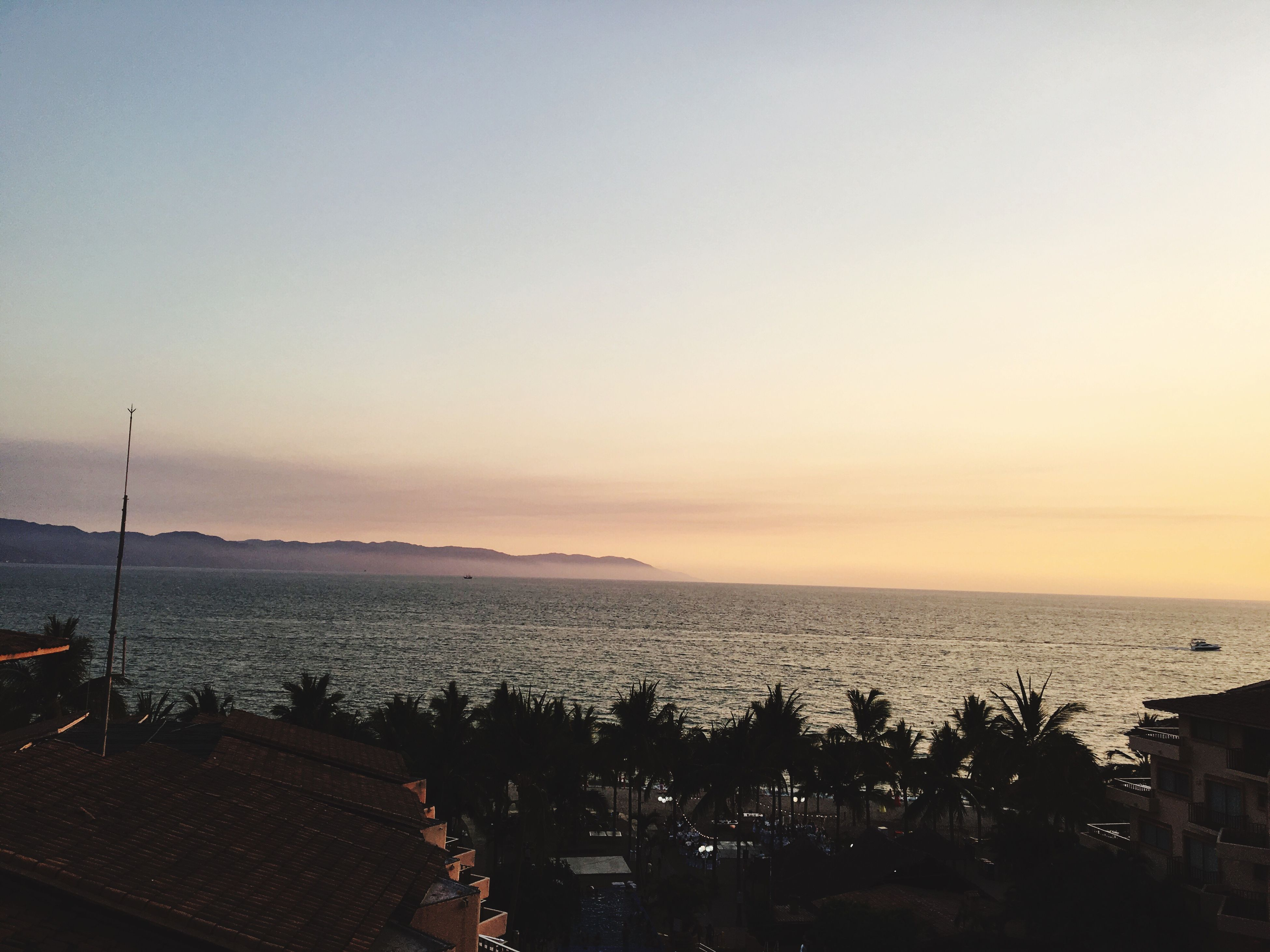 sea, sunset, horizon over water, water, clear sky, copy space, high angle view, scenics, building exterior, orange color, sky, beauty in nature, nature, built structure, architecture, tranquil scene, tranquility, cityscape, city, dusk