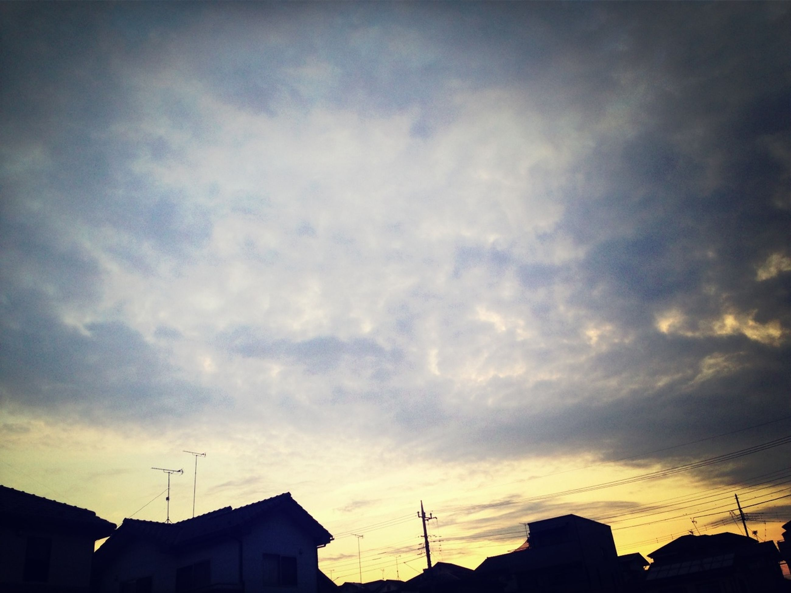 building exterior, architecture, built structure, low angle view, sky, house, sunset, residential structure, cloud - sky, silhouette, high section, residential building, power line, building, cloud, cloudy, roof, outdoors, no people, cable