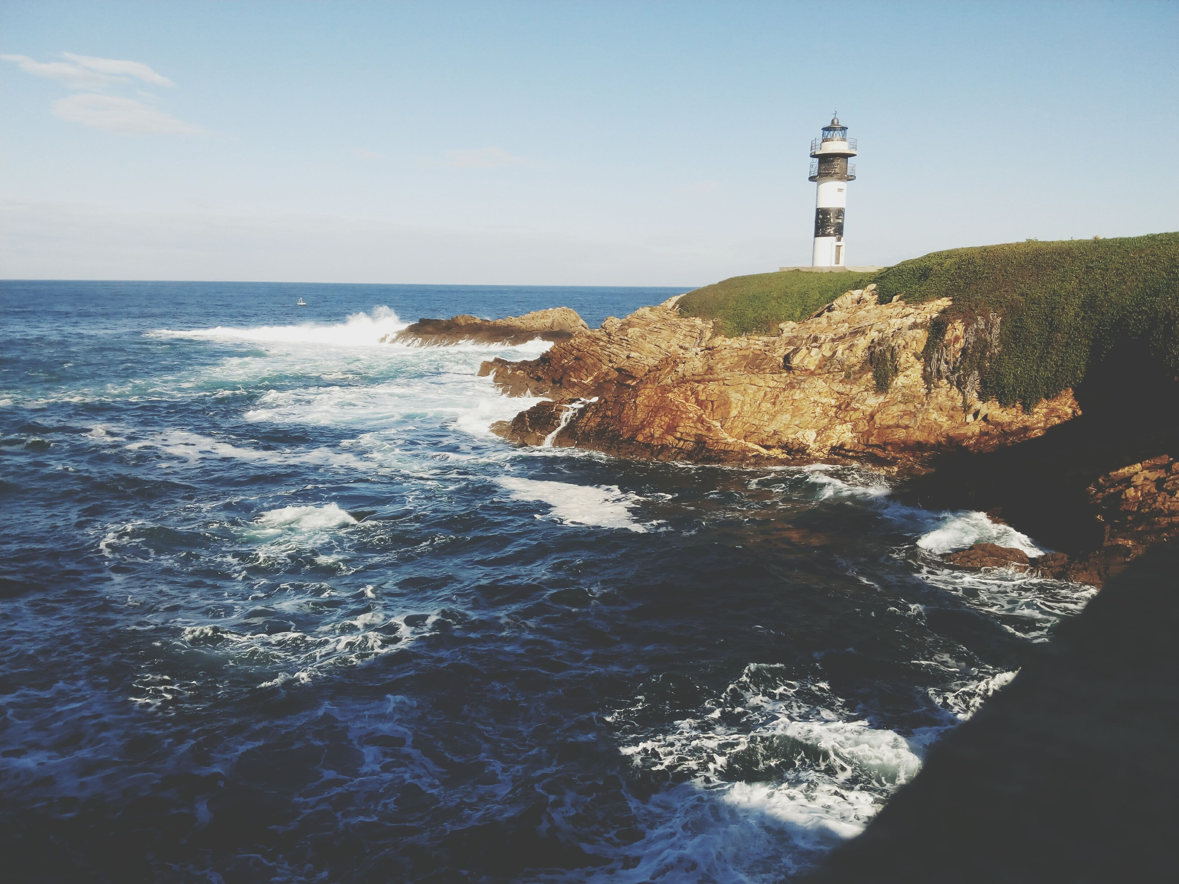 sea, water, horizon over water, lighthouse, guidance, tranquil scene, tranquility, protection, scenics, built structure, sky, clear sky, nature, direction, beauty in nature, safety, architecture, rippled, blue, day