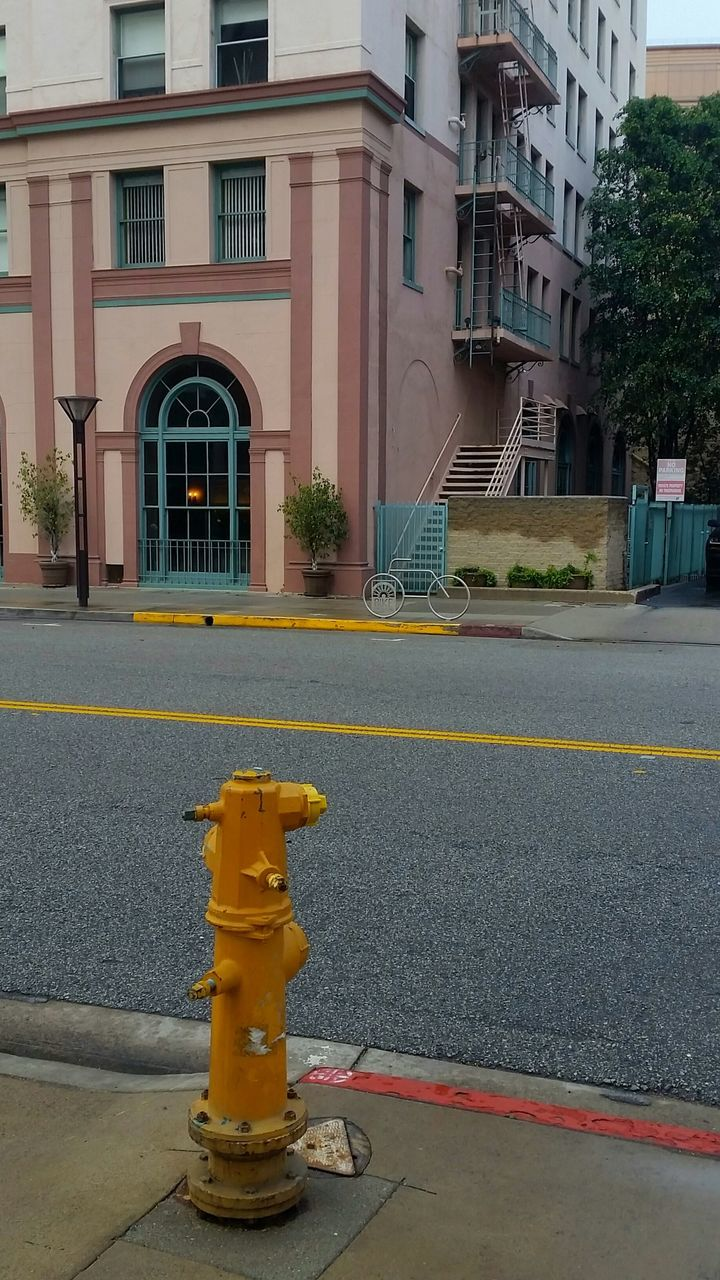 yellow, building exterior, architecture, built structure, street, safety, no people, outdoors, day, road, residential building, city, traffic cone, sky, close-up