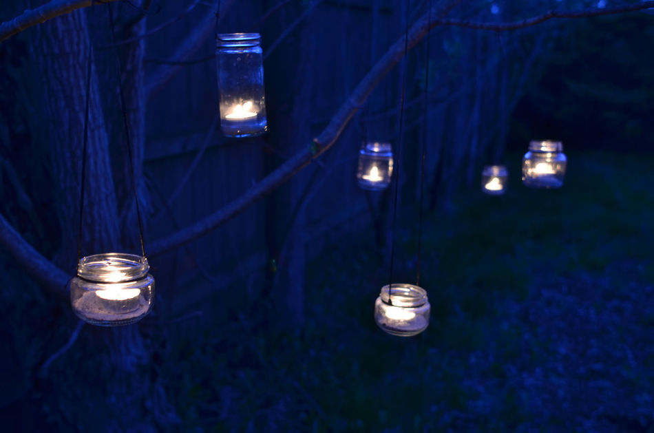 night scene with candles in jars hanging from tree branches Branches Branches Of Trees Candlelight Candles Hanging Illuminated Jars  Jars Of Lights Night Night Lights No People Outdoors Spring Trees