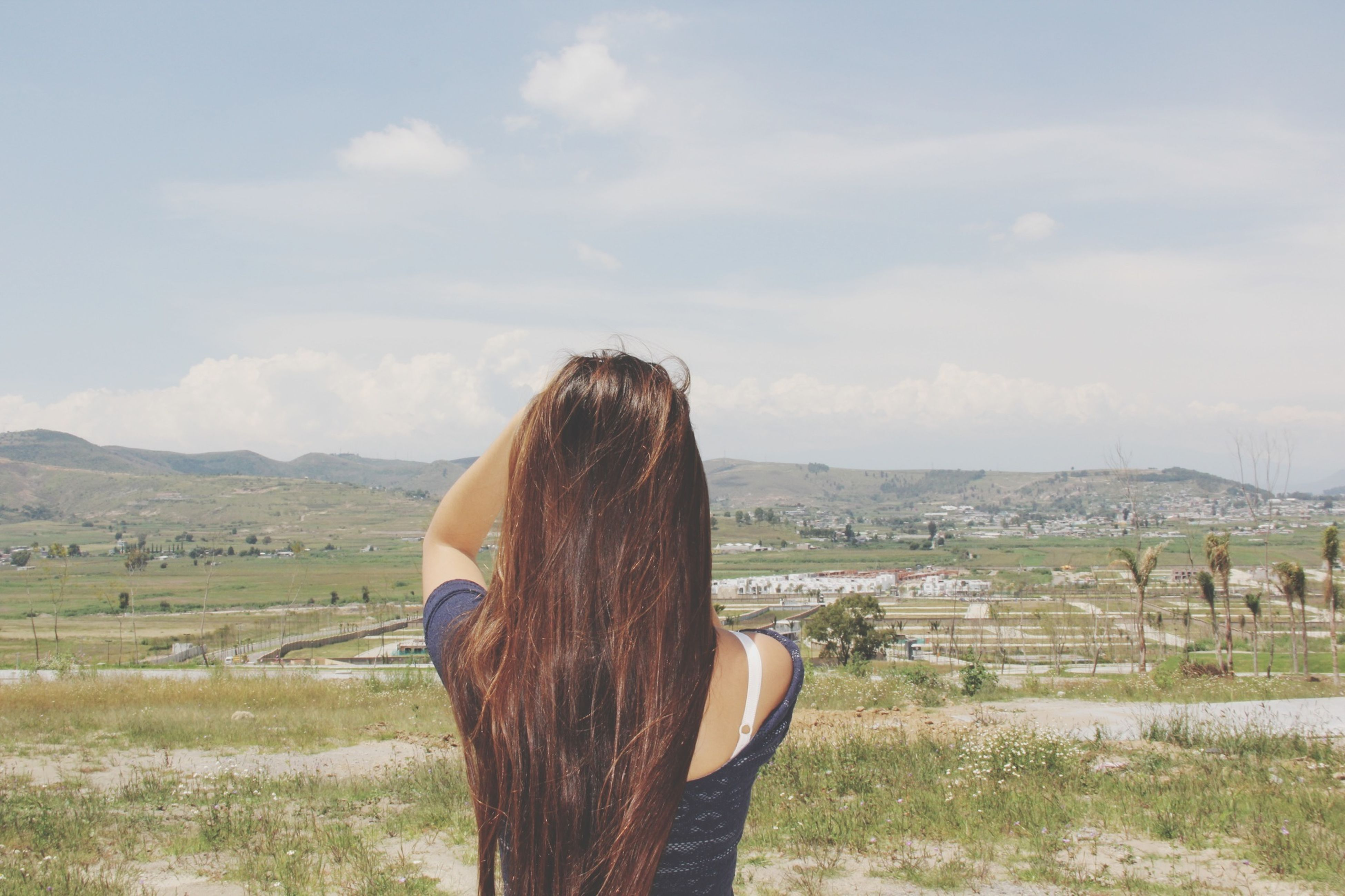 long hair, landscape, sky, mountain, lifestyles, rear view, young adult, young women, person, leisure activity, field, tranquility, tranquil scene, casual clothing, nature, grass, standing, scenics