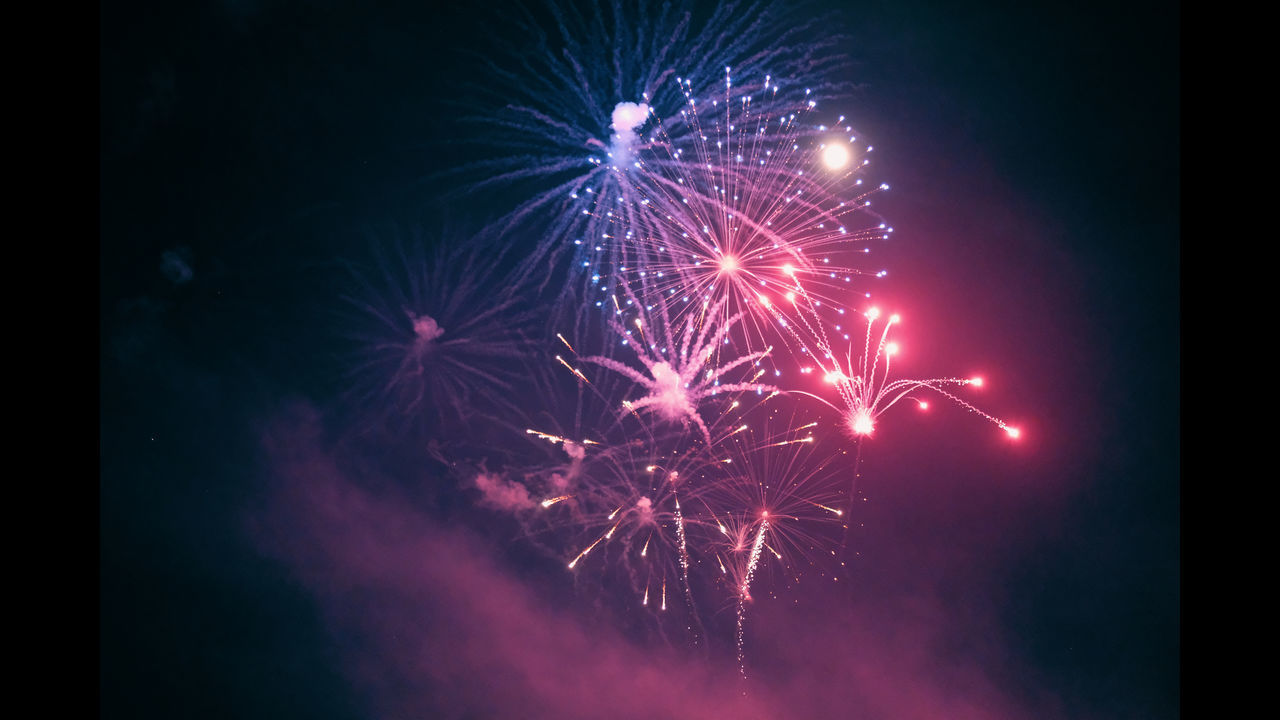 firework display, celebration, night, firework - man made object, exploding, arts culture and entertainment, long exposure, event, low angle view, glowing, smoke - physical structure, illuminated, motion, sky, firework, multi colored, blurred motion, no people, outdoors