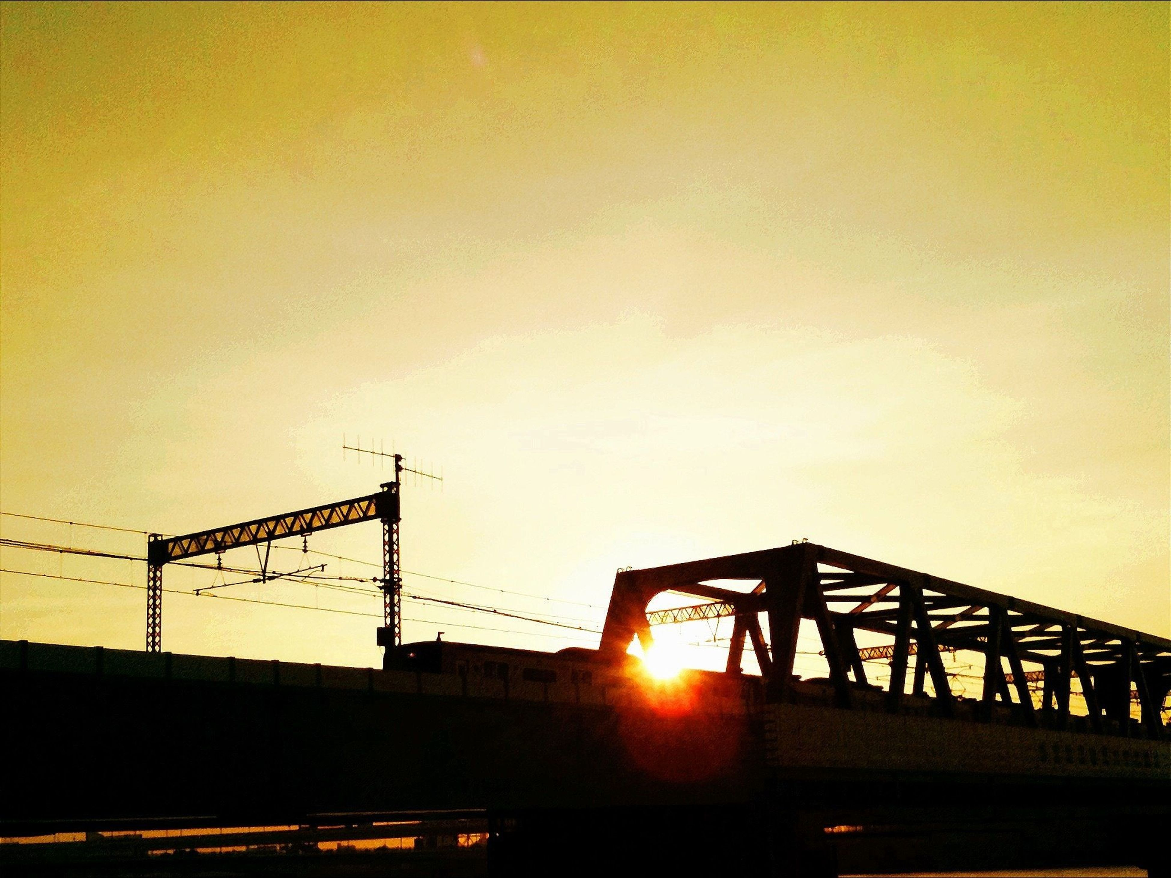 sunset, transportation, connection, bridge - man made structure, sun, built structure, architecture, orange color, silhouette, sky, copy space, engineering, bridge, clear sky, railing, sunlight, car, land vehicle, outdoors, road