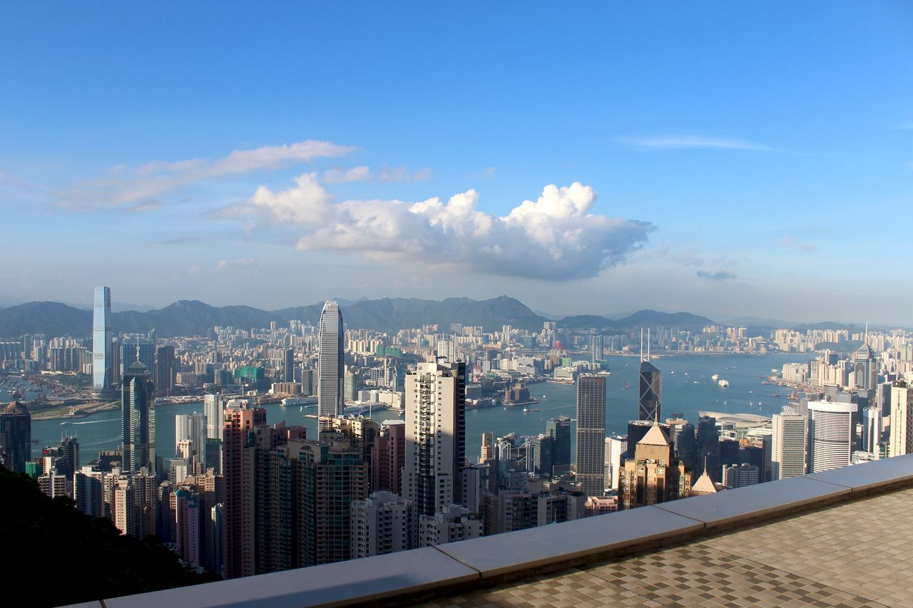 architecture, cityscape, city, skyscraper, building exterior, built structure, sky, modern, travel destinations, water, cloud - sky, outdoors, sea, no people, urban skyline, day, mountain, nature