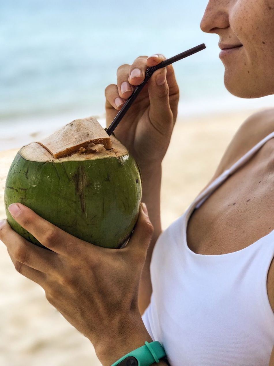 One Person Sea Sand Human Hand Beach Real People Holding Sky Human Body Part Day Leisure Activity Close-up Vacations Outdoors Women Young Adult Water Young Women Adults Only People Smiling Coconut Drinking Tropical Paradise Tropical Climate