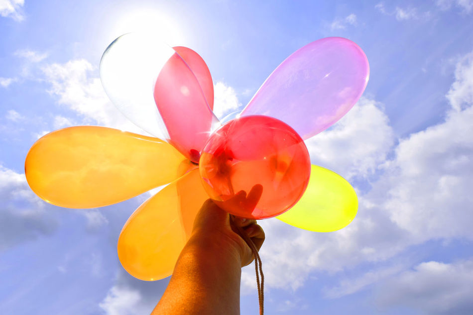 Balloon Blue Bubble Wand Celebration Close-up Cloud - Sky Day Fragility Helium Balloon Holding Human Body Part Human Finger Human Hand Lifestyles Low Angle View Multi Colored One Person Outdoors Real People Red Ribbon Sky Sunlight Unrecognizable Person Yellow
