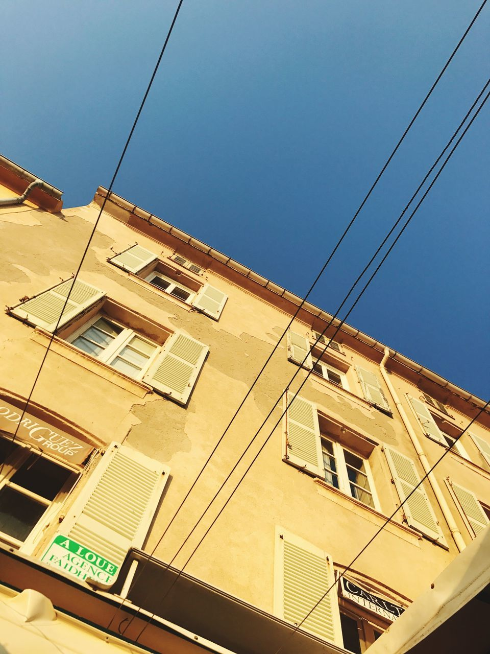 architecture, cable, building exterior, built structure, low angle view, window, residential building, outdoors, no people, day, sky, clear sky