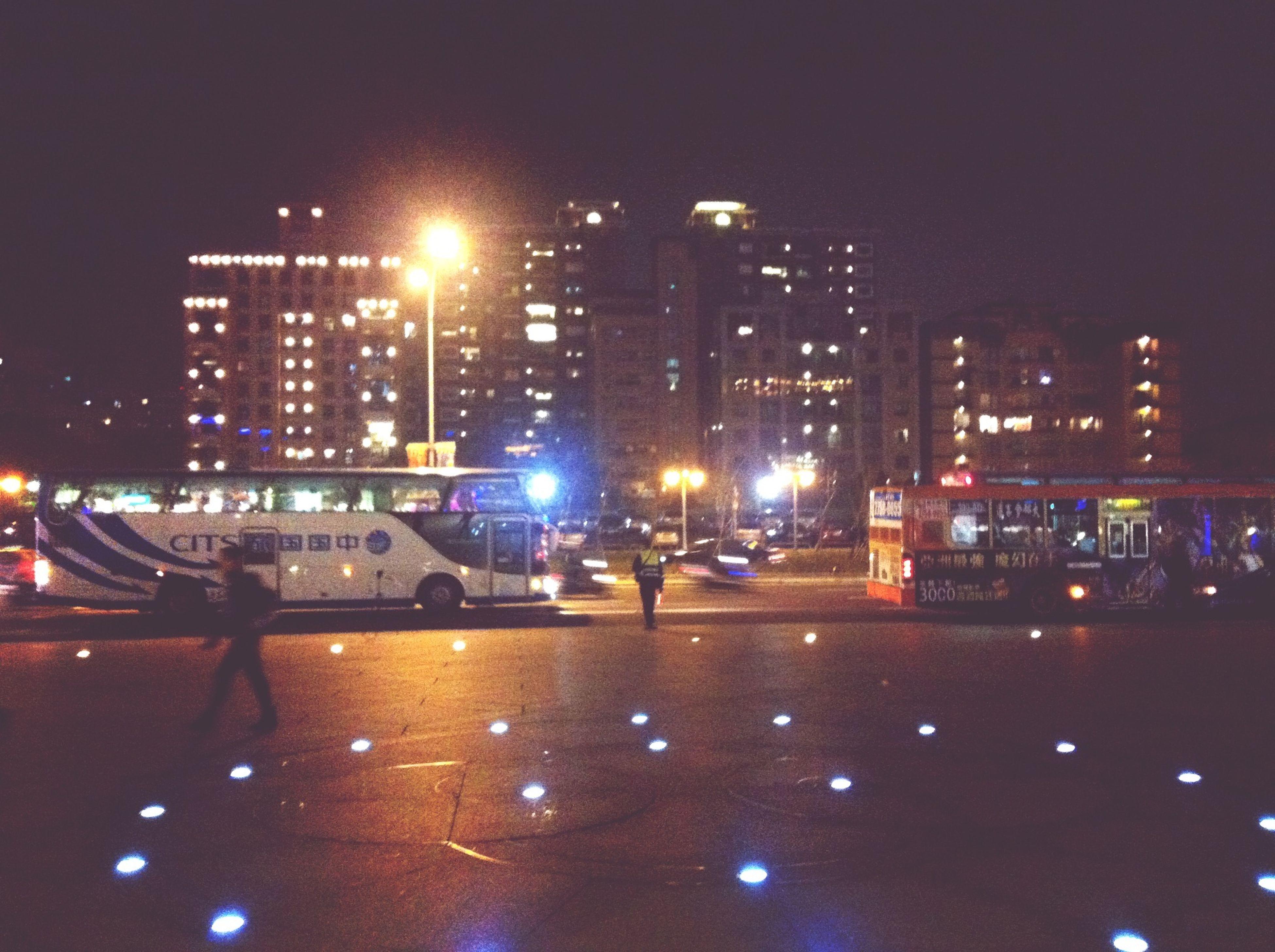illuminated, building exterior, architecture, city, night, built structure, transportation, street light, skyscraper, mode of transport, cityscape, city life, car, office building, modern, land vehicle, street, city street, lighting equipment, tall - high