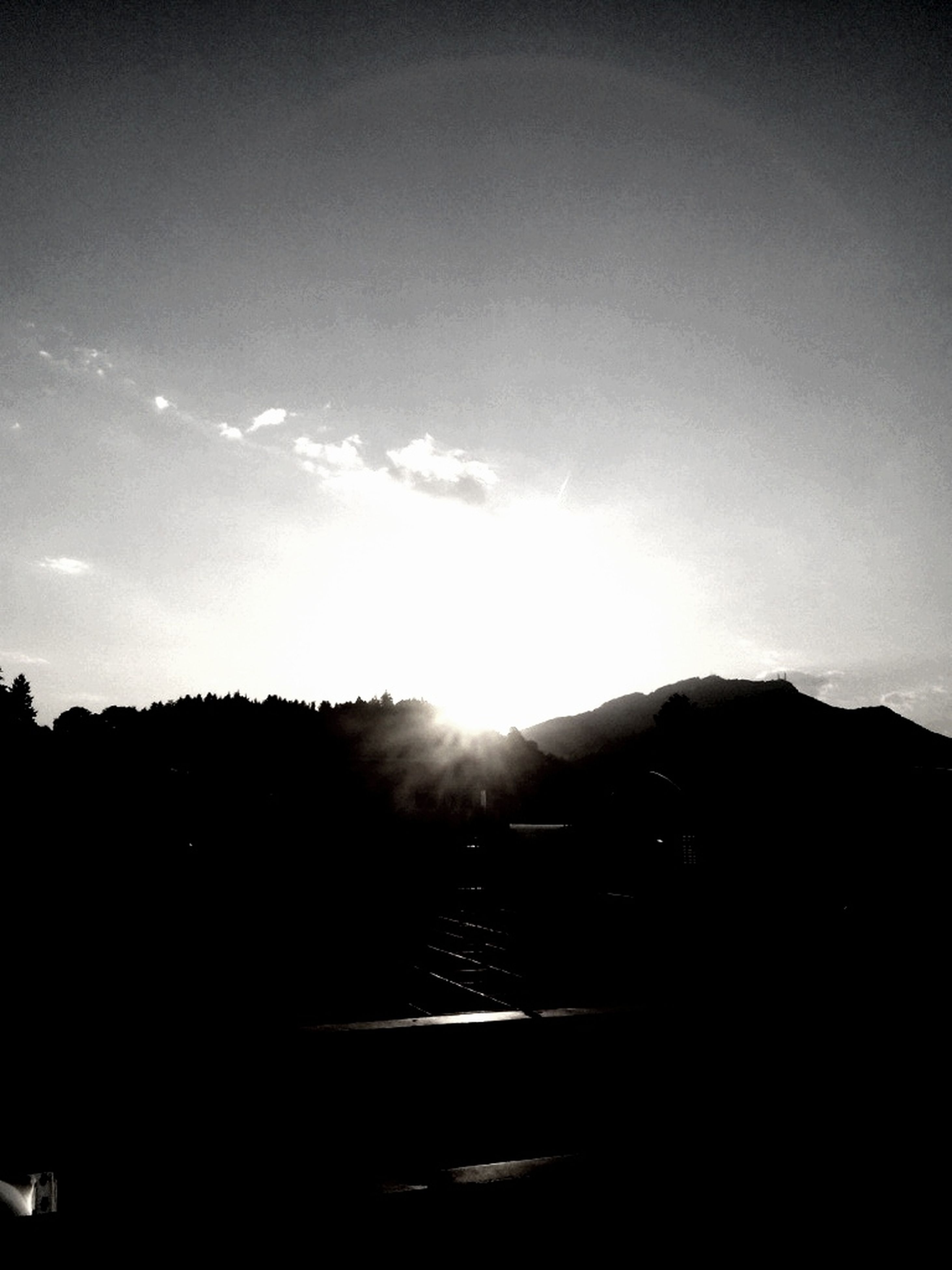 silhouette, sun, mountain, sky, sunbeam, sunlight, scenics, tranquility, tranquil scene, beauty in nature, lens flare, nature, mountain range, cloud - sky, landscape, sunset, cloud, outdoors, idyllic, copy space