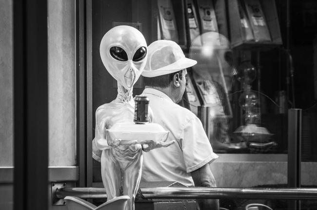 Chip shop near central station... I don't know why they picked an alien mascot. Alien Candid Central Station Chip Shop Day Fast Food Grey Hat Irn Bru People Portrait Reflection Scotland Scottish Shop Street The Shop Around The Corner Unrecognizable Person Window Fine Art Photography Battle Of The Cities People And Places Monochrome Photography