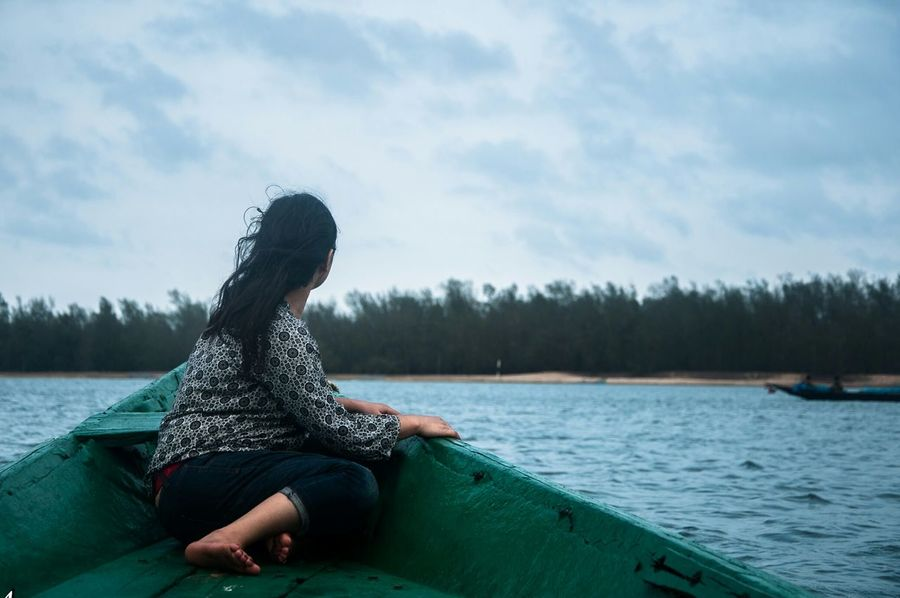EyeEmNewHere One Woman Only One Person Sitting One Young Woman Only Relaxation Water Long Hair Young Adult Leisure Activity Rear View Vacations Beauty In Nature Tranquility People Backside Backside Portrait Cloud - Sky Day Boat Green Boat Facing Away