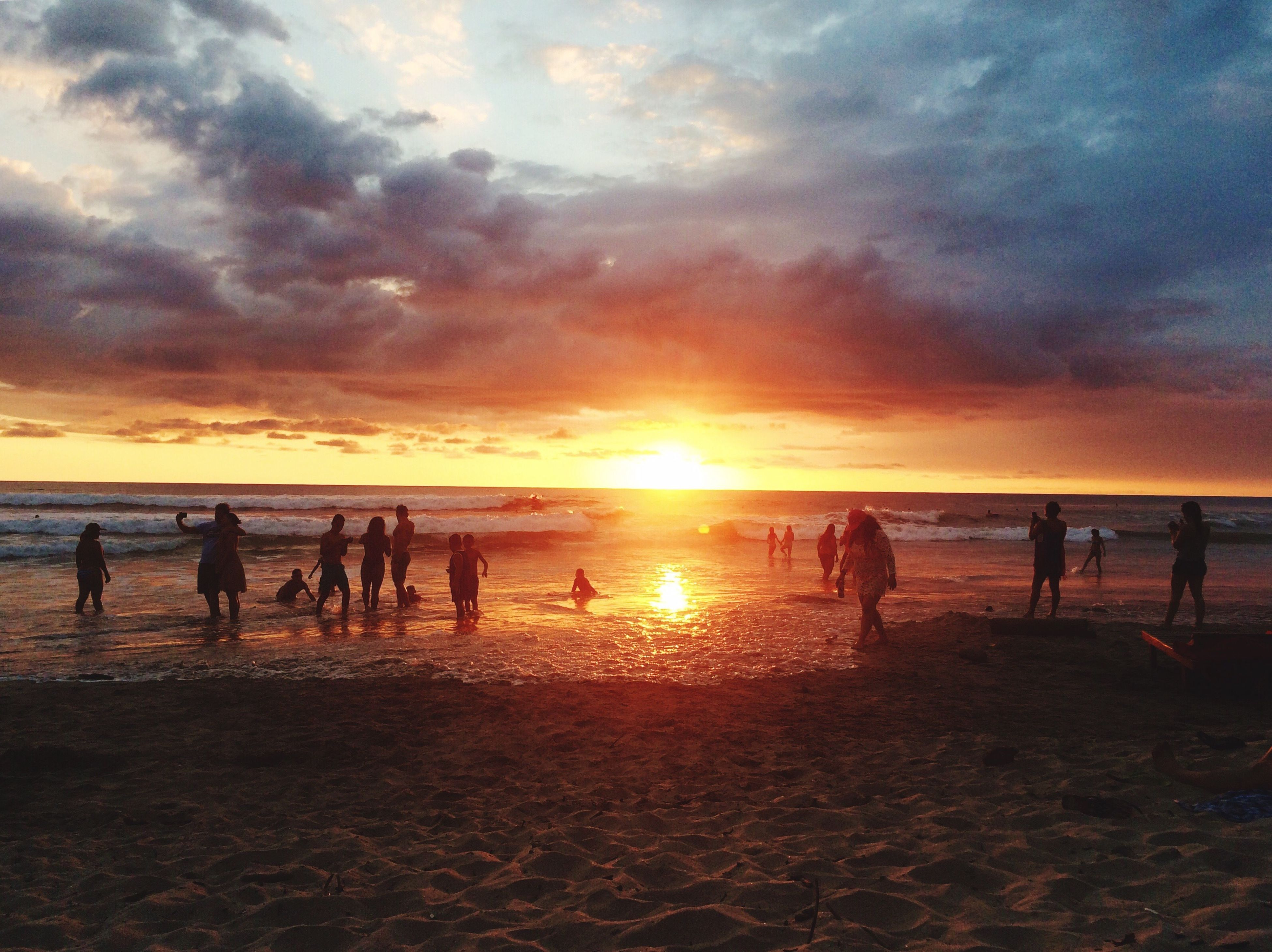 sunset, beach, sea, sky, orange color, sand, nature, real people, horizon over water, water, outdoors, beauty in nature, cloud - sky, friendship, beach volleyball, people, large group of people, adults only, togetherness, adult, day