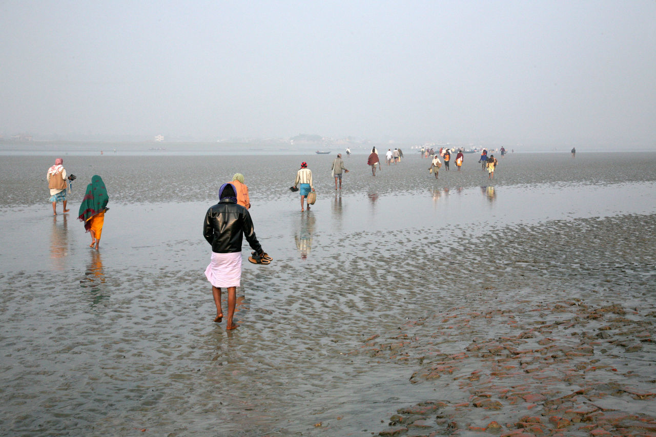 During low tide the water in the river Malta falls so low that people walk to the other shore in Canning Town, India on January 17, 2009. India Canning Canning Town Coast Ebb Low Low Tide Malta River Mud Nature People Shore Tidal Tide Town Walk Walking Water West Bengal