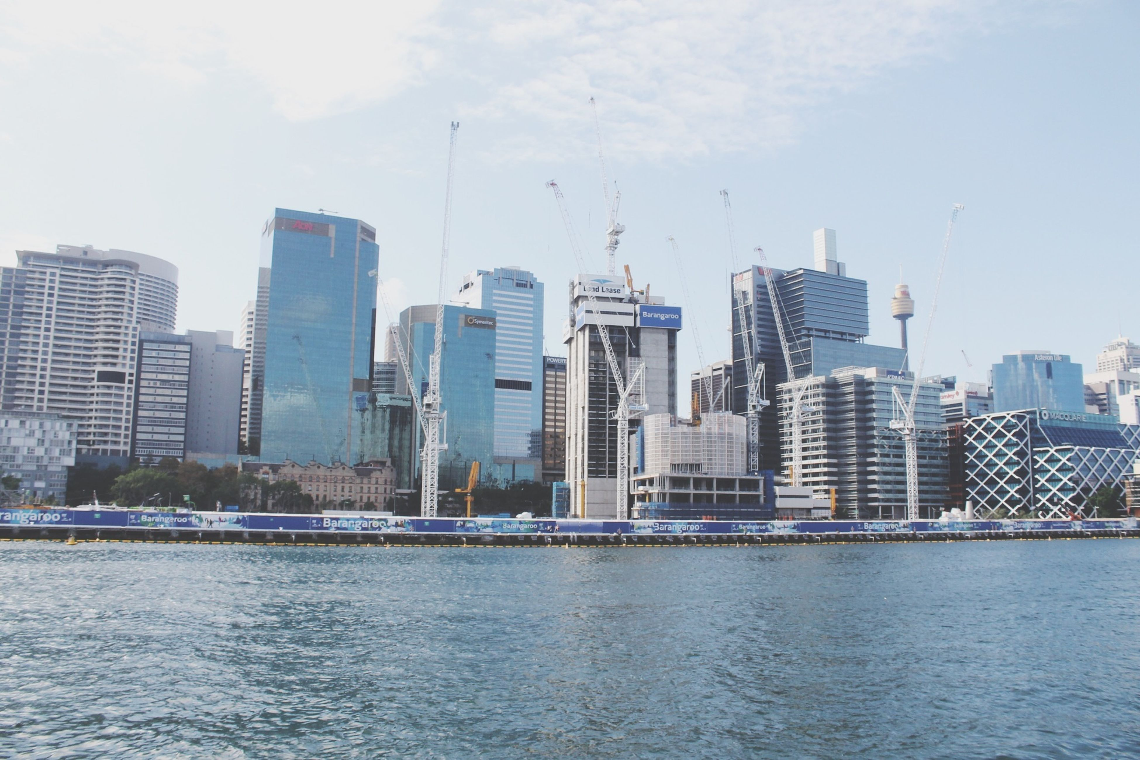 building exterior, city, skyscraper, architecture, built structure, cityscape, water, urban skyline, office building, waterfront, tall - high, modern, sky, river, tower, financial district, development, skyline, tall, sea