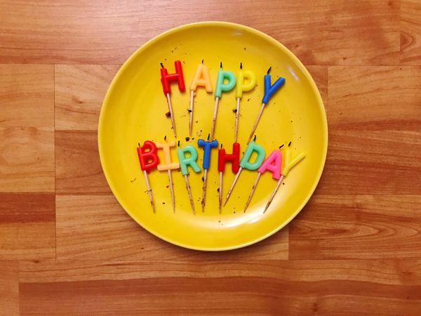 Table Food And Drink Plate High Angle View No People Wood - Material Yellow Indoors  Multi Colored Text Birthday Candles Directly Above Birthday Cake