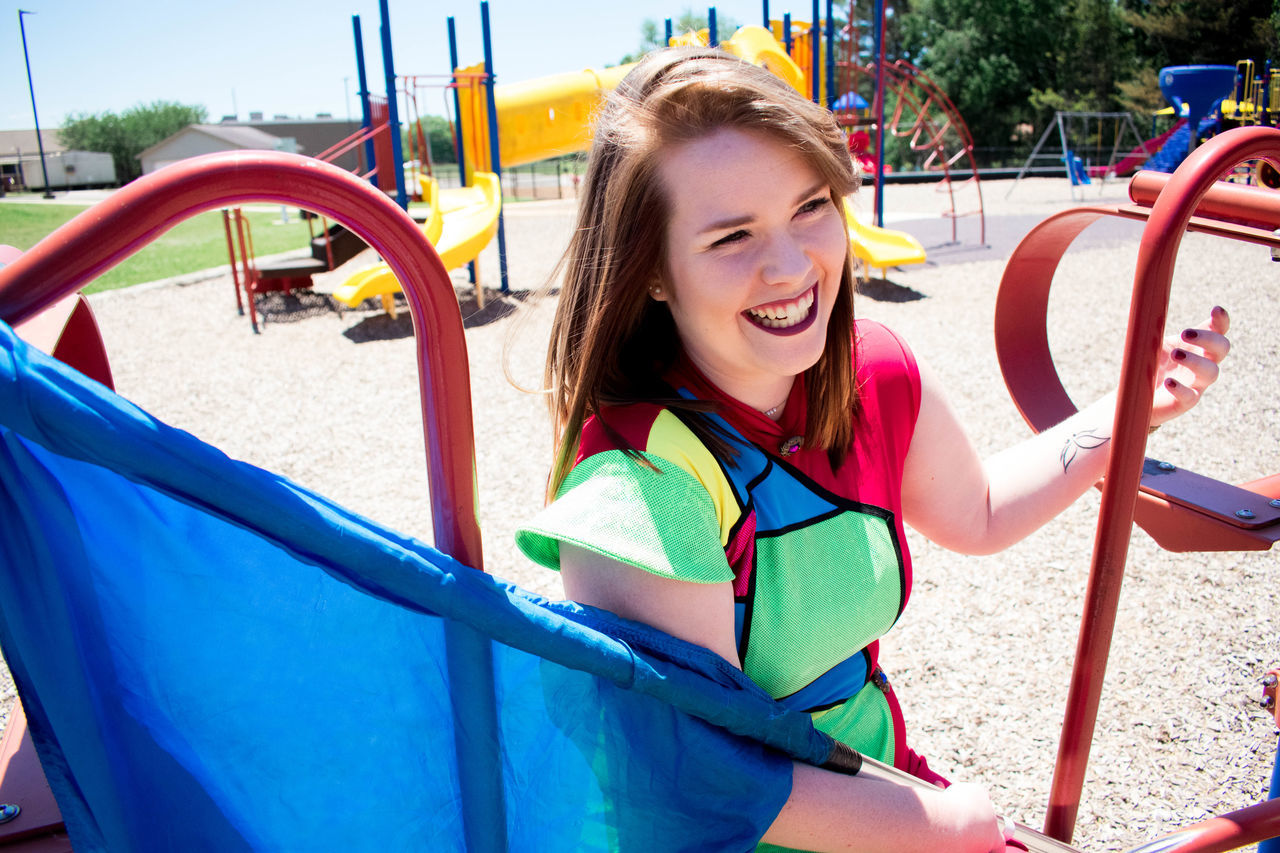 Casual Clothing Cheerful Childhood Day Elementary Age Enjoyment Fun Girls Happiness Leisure Activity Lifestyles Merry-go-round Nature One Person Outdoor Play Equipment Outdoors Park Park - Man Made Space People Playground Playing Portrait Smiling Young Adult Young Women
