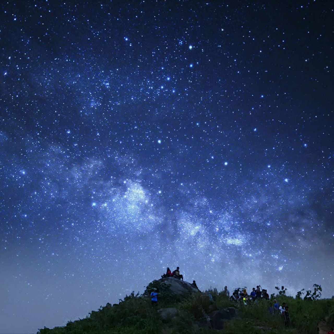 Low Angle View Of People On Mountain Against Star Field