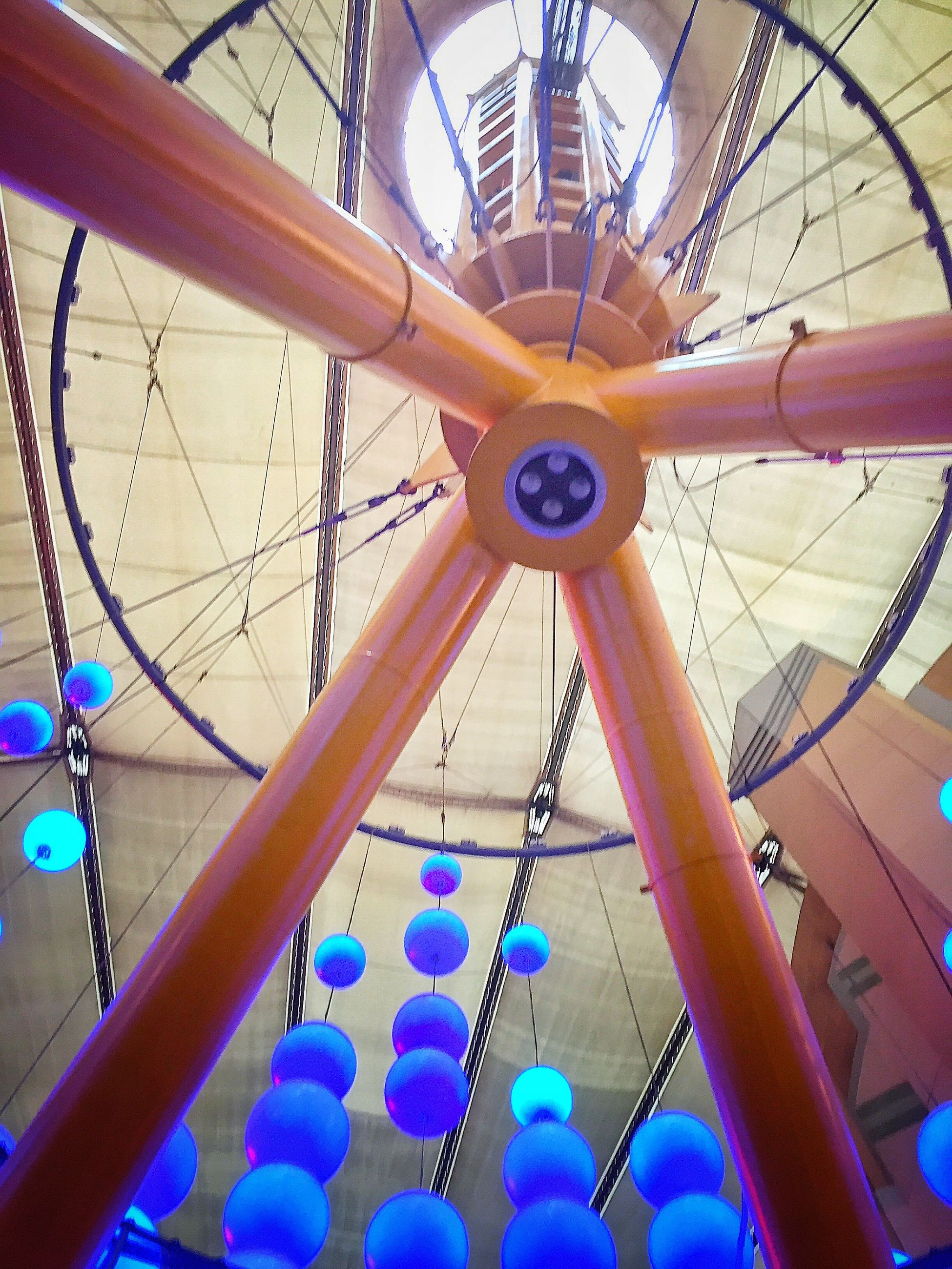 low angle view, metal, amusement park, indoors, ceiling, amusement park ride, circle, metallic, built structure, ferris wheel, arts culture and entertainment, wheel, architecture, pattern, design, blue, day, no people, railing, close-up