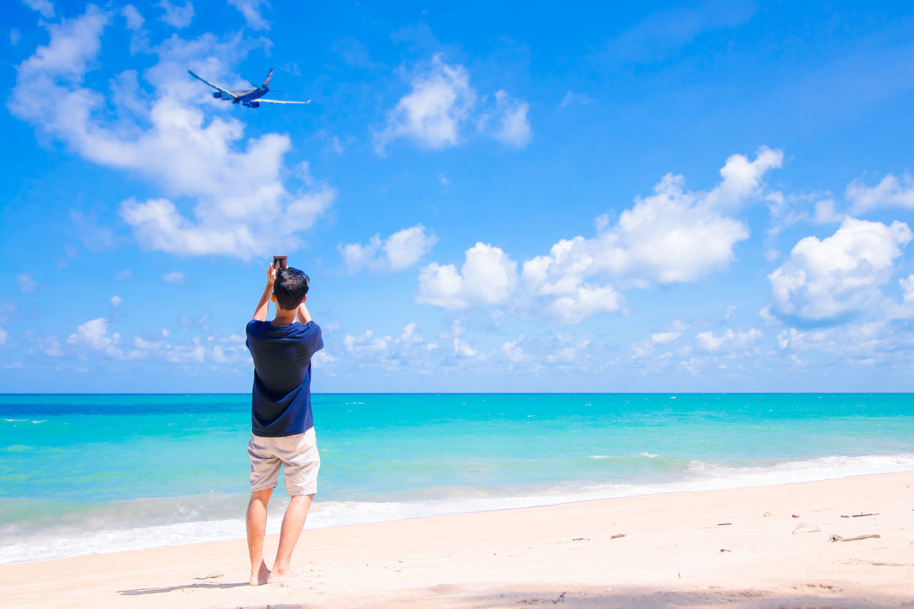 sea, beach, horizon over water, sand, sky, nature, shore, beauty in nature, blue, one person, scenics, full length, real people, standing, water, cloud - sky, rear view, leisure activity, vacations, day, outdoors, adult, people