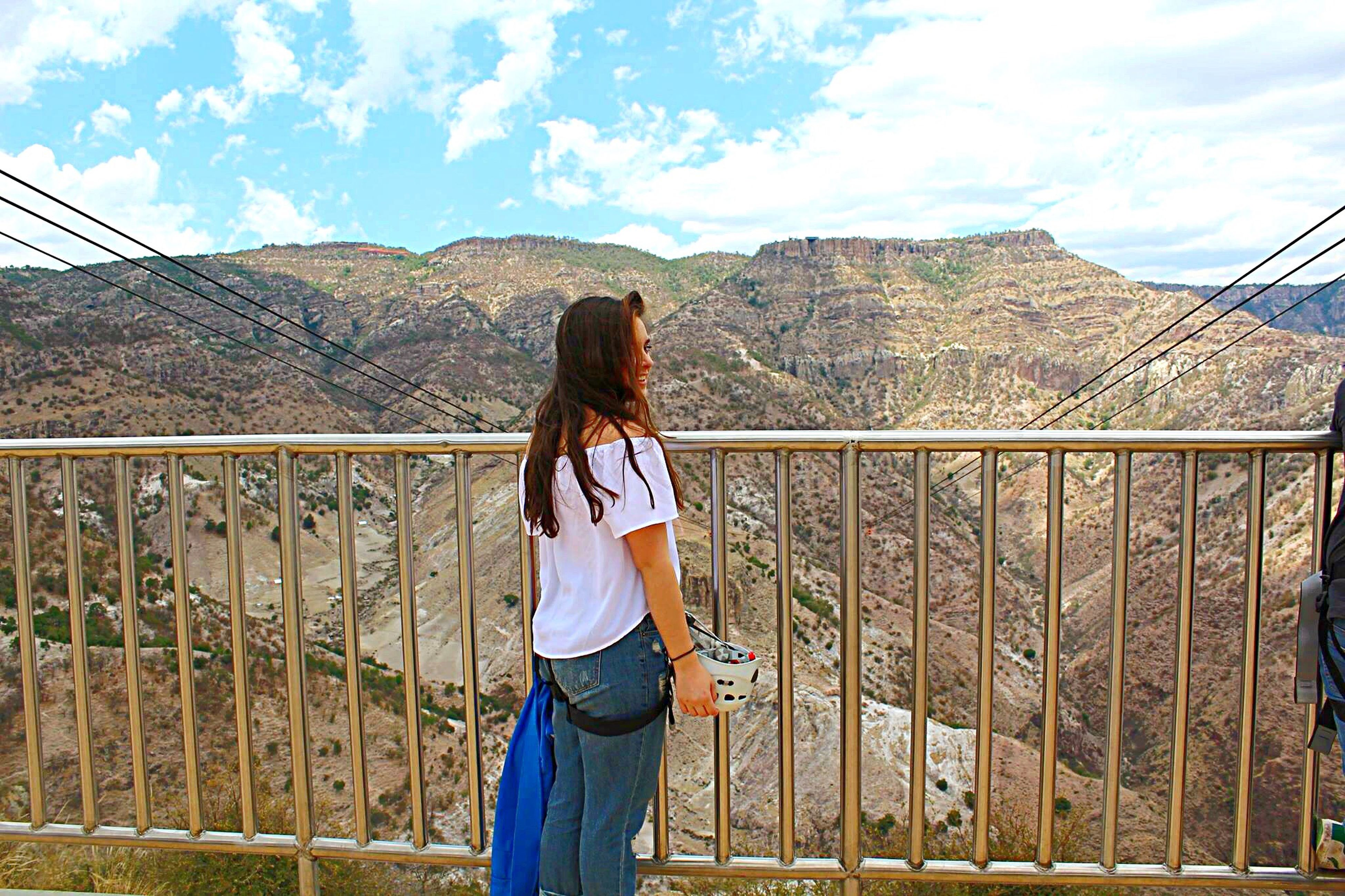 rear view, lifestyles, casual clothing, standing, mountain, leisure activity, full length, sky, three quarter length, railing, young adult, person, cloud - sky, men, mountain range, cloud, long hair, waist up