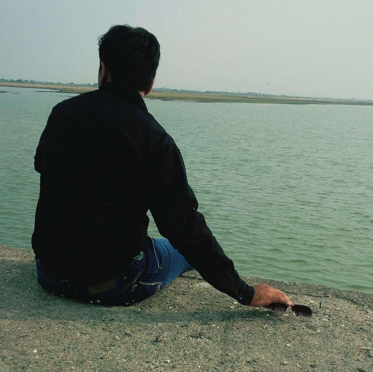 real people, sea, one person, water, rear view, sitting, full length, outdoors, men, leisure activity, standing, horizon over water, casual clothing, lifestyles, nature, day, tranquil scene, weekend activities, vacations, tranquility, beach, clear sky, scenics, beauty in nature, sky, fishing pole, one man only, adult, people