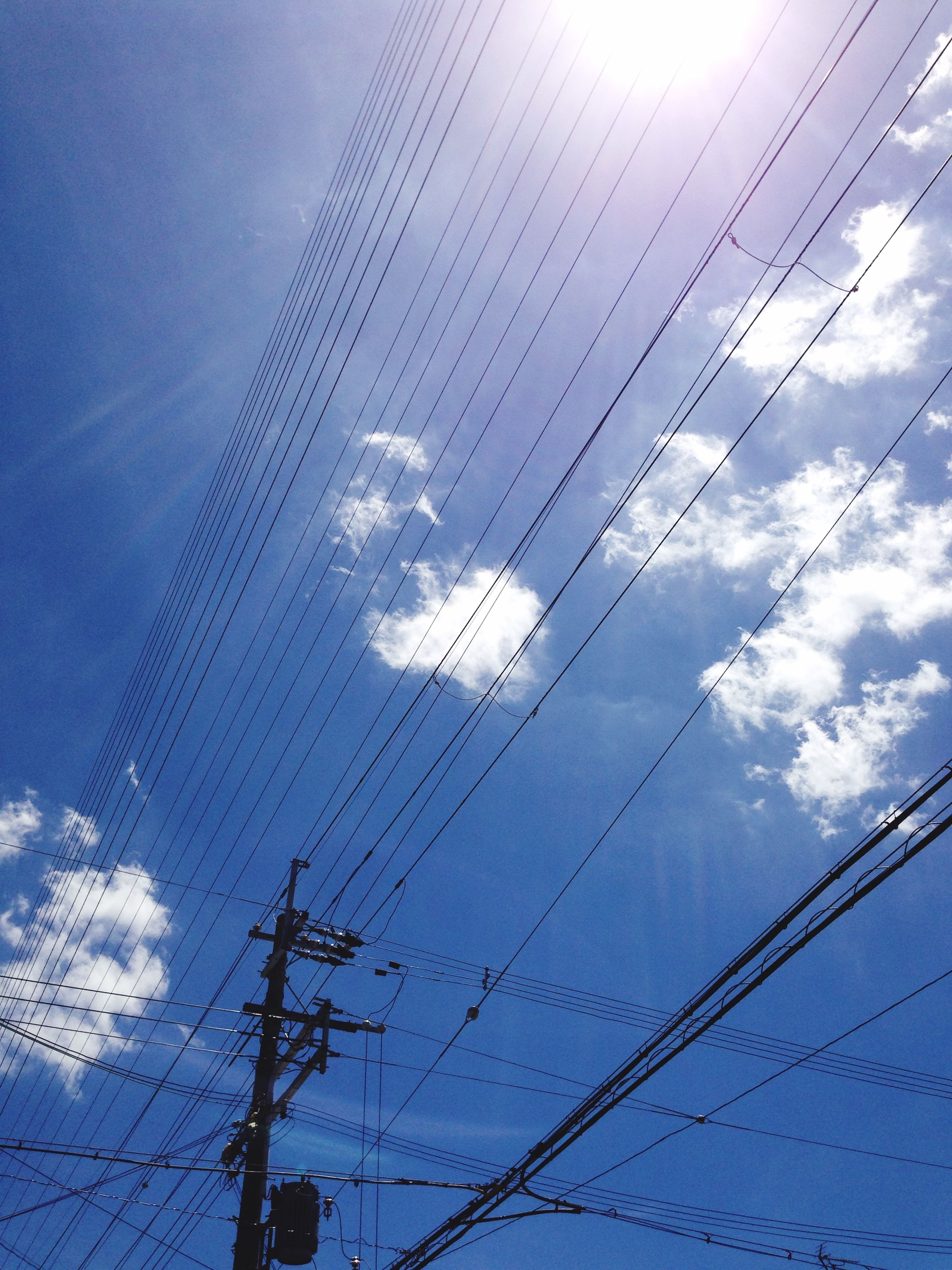 low angle view, sky, power line, cable, blue, connection, electricity, cloud - sky, built structure, electricity pylon, architecture, cloud, day, power supply, technology, outdoors, no people, cloudy, modern, tall - high