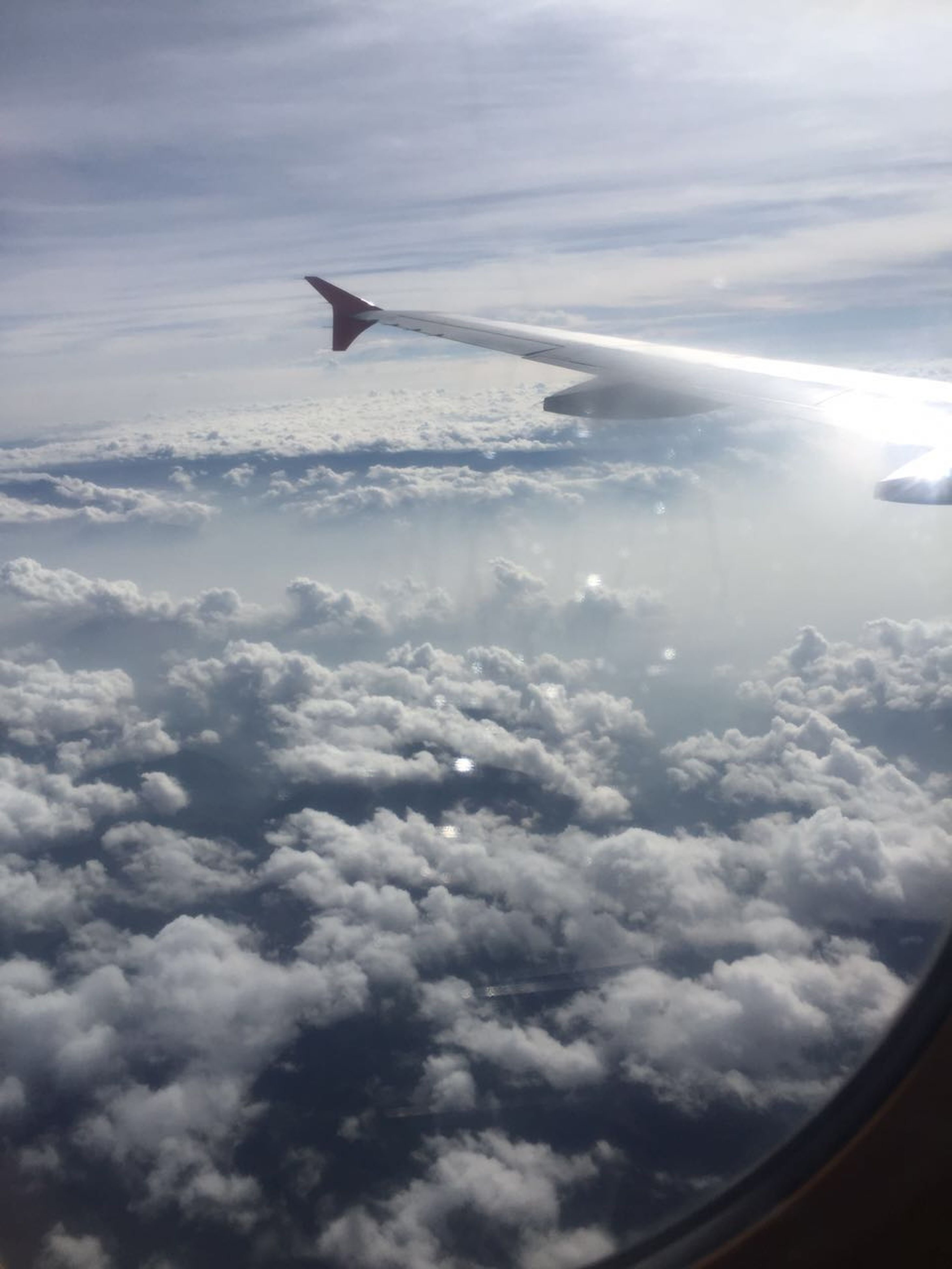airplane, flying, air vehicle, transportation, aircraft wing, mode of transport, aerial view, part of, sky, mid-air, cropped, cloud - sky, travel, scenics, public transportation, cloudscape, journey, on the move, beauty in nature, landscape