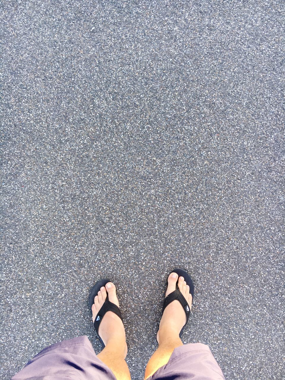 low section, human leg, standing, shoe, personal perspective, high angle view, directly above, outdoors, human body part, real people, one person, day, asphalt, lifestyles, road, men, nature, one man only, adult, people