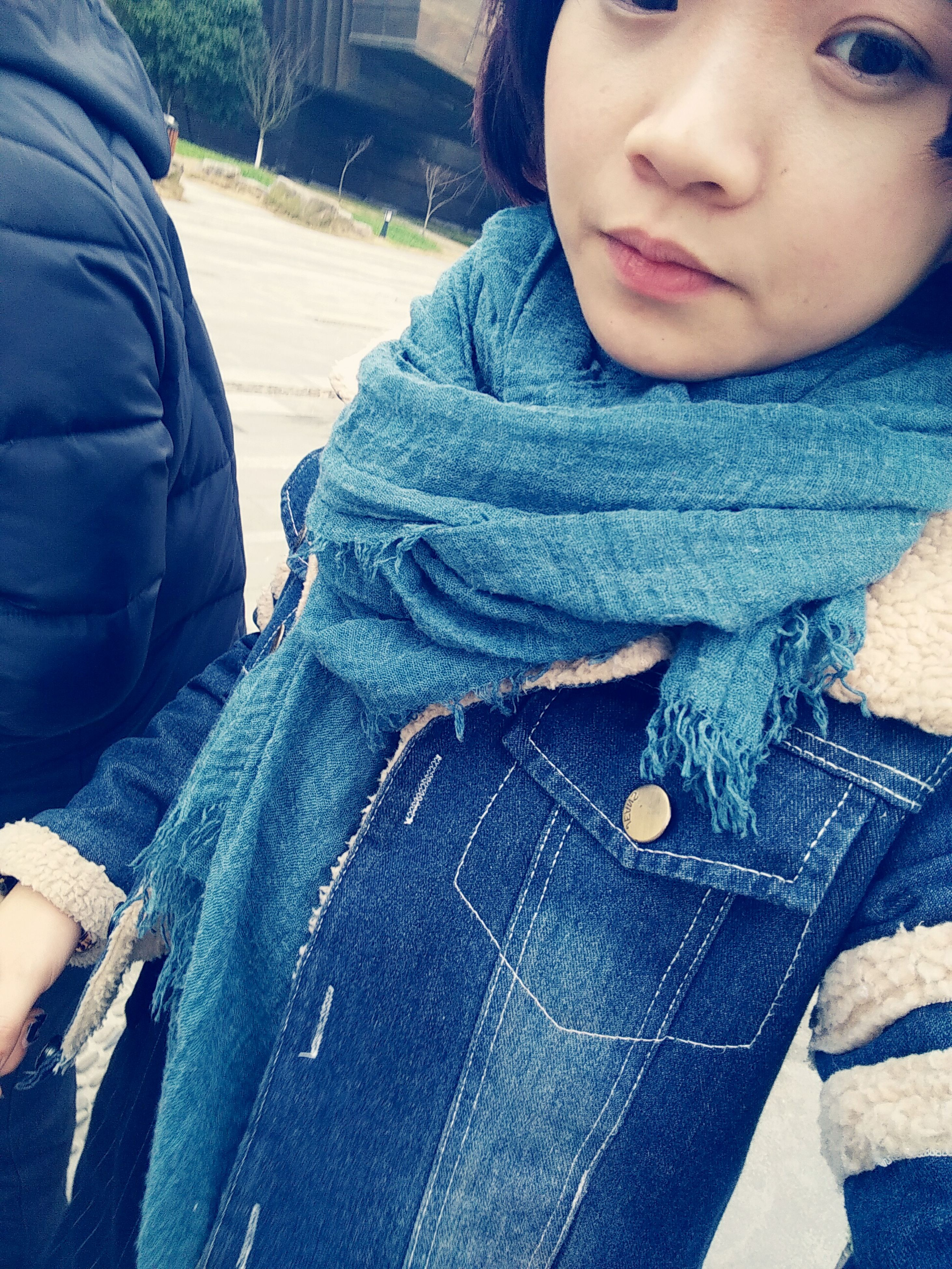 casual clothing, lifestyles, indoors, leisure activity, midsection, person, front view, childhood, jeans, high angle view, close-up, jacket, warm clothing, sitting, relaxation, holding, day