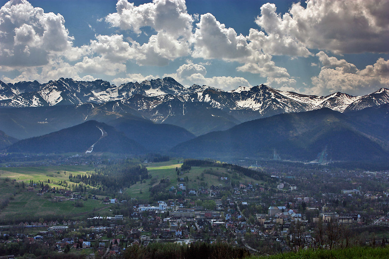 Clouds Over Mountain Range With Town In Foreground
