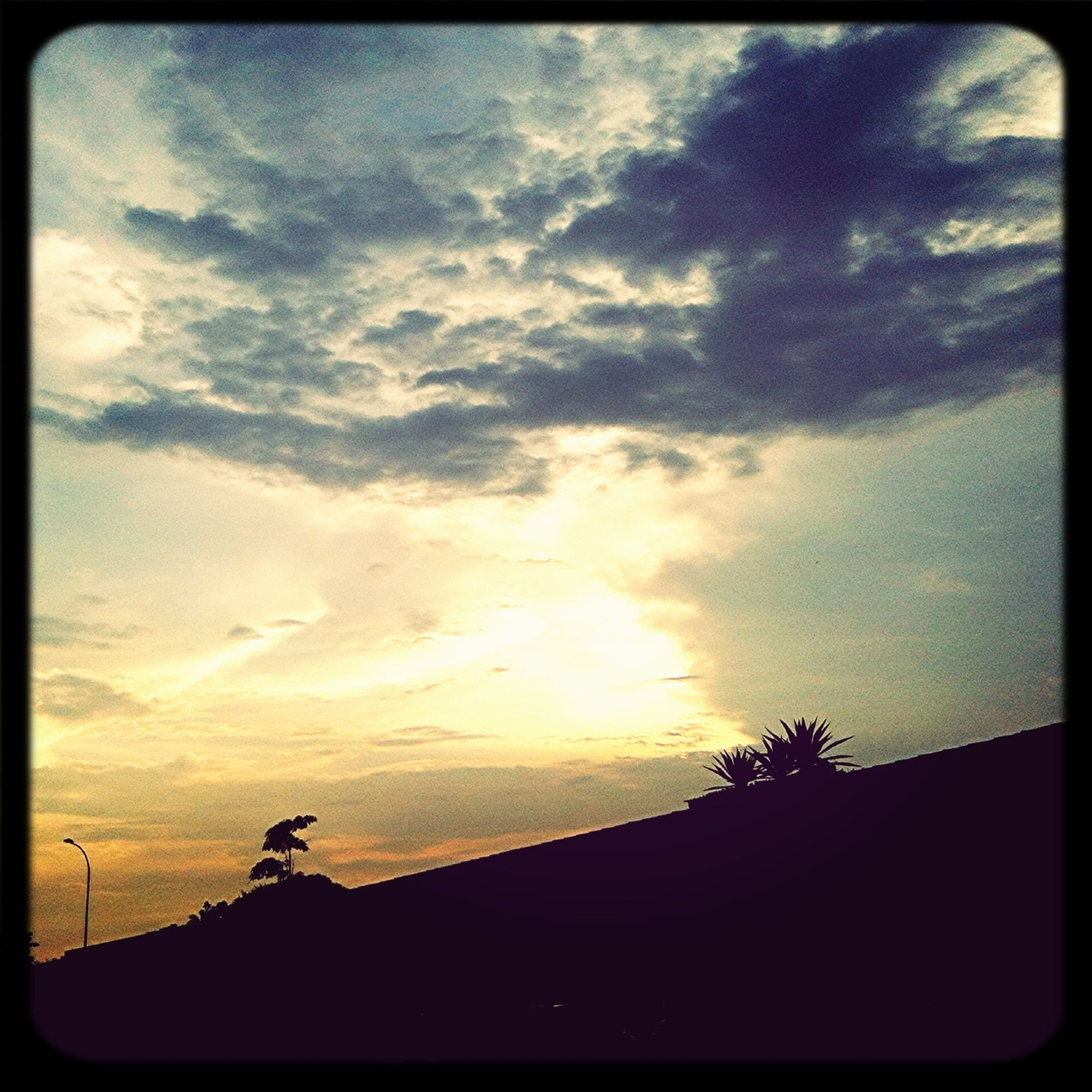 silhouette, sky, sunset, low angle view, cloud - sky, transfer print, auto post production filter, beauty in nature, cloud, tree, scenics, nature, tranquility, cloudy, built structure, tranquil scene, dusk, outdoors, building exterior, no people