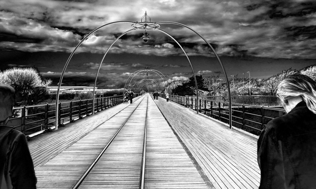The long walk ahead Black And White Photography Couple Walking Dramatic Sky Geometric Composition Long Walk Monochrome People On Pier Perspactive On Pier Pier Southport Pier Strangers Symmetrical Walking The Pier