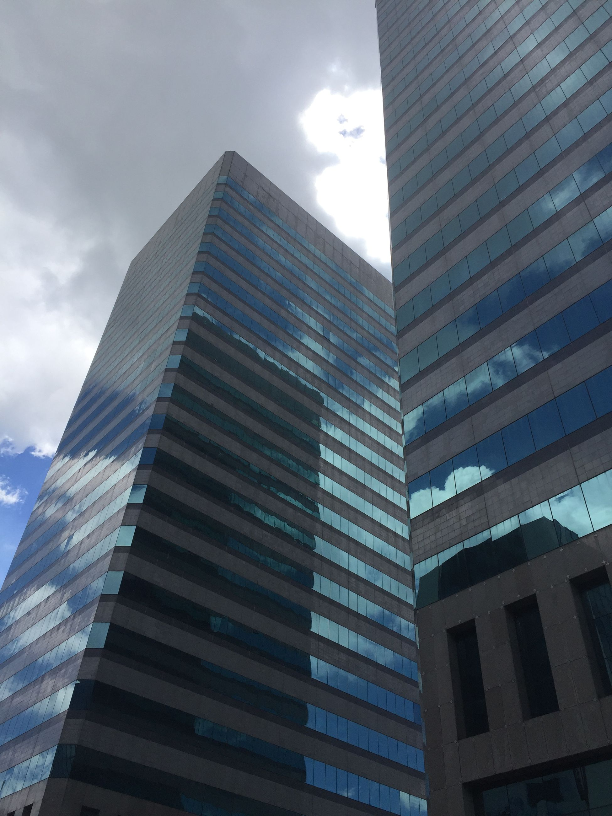 architecture, built structure, building exterior, low angle view, reflection, modern, office building, sky, city, building, skyscraper, glass - material, tall - high, cloud - sky, tower, day, sunlight, outdoors, no people, directly below