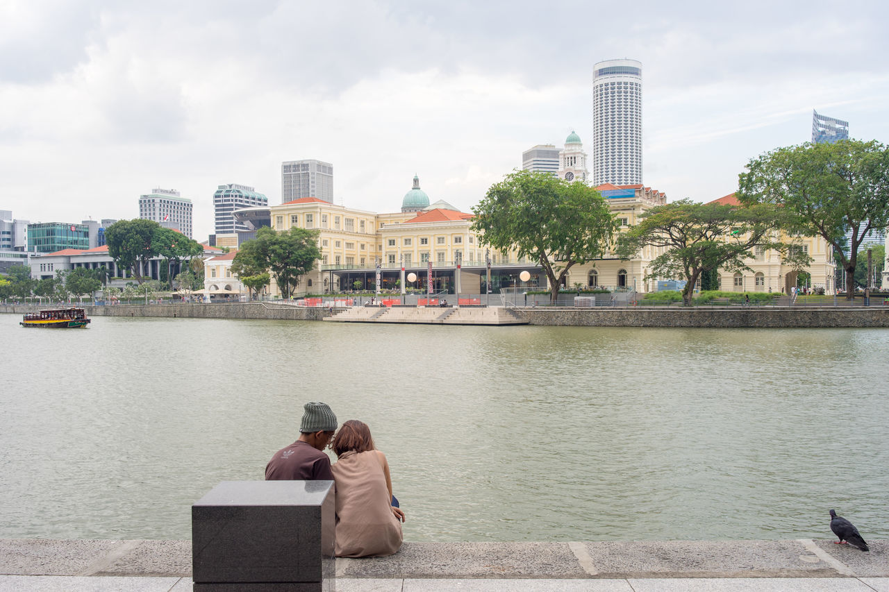 A young couple are sitting closely, with a pigeon wandering around, at waterfront of Raffle Place, the financial center of Singapore, facing Singapore River and Asian Civilisation Museum, in late afternoon. Afternoon Asian Civilisation Attraction Boat Building City Cloud Countryside Cruising Evening Girl Intimate Landmark Lifestyles Museum Pigeon Raffles Place River Singapore Singapore River Sitting Sky Travel Water Young Adult