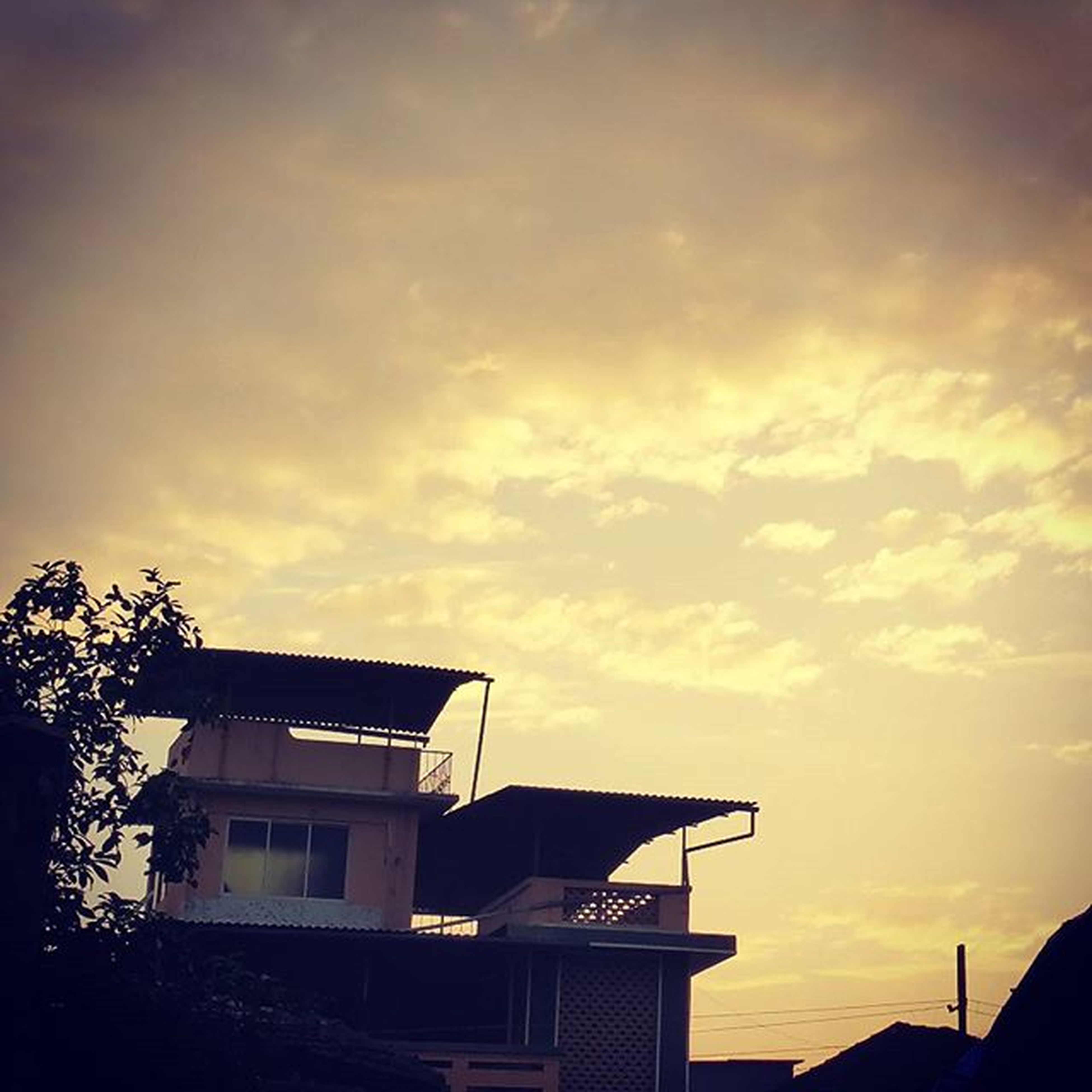sunset, building exterior, built structure, architecture, sky, house, cloud - sky, silhouette, residential structure, orange color, low angle view, cloud, beauty in nature, residential building, nature, roof, cloudy, scenics, outdoors, tree