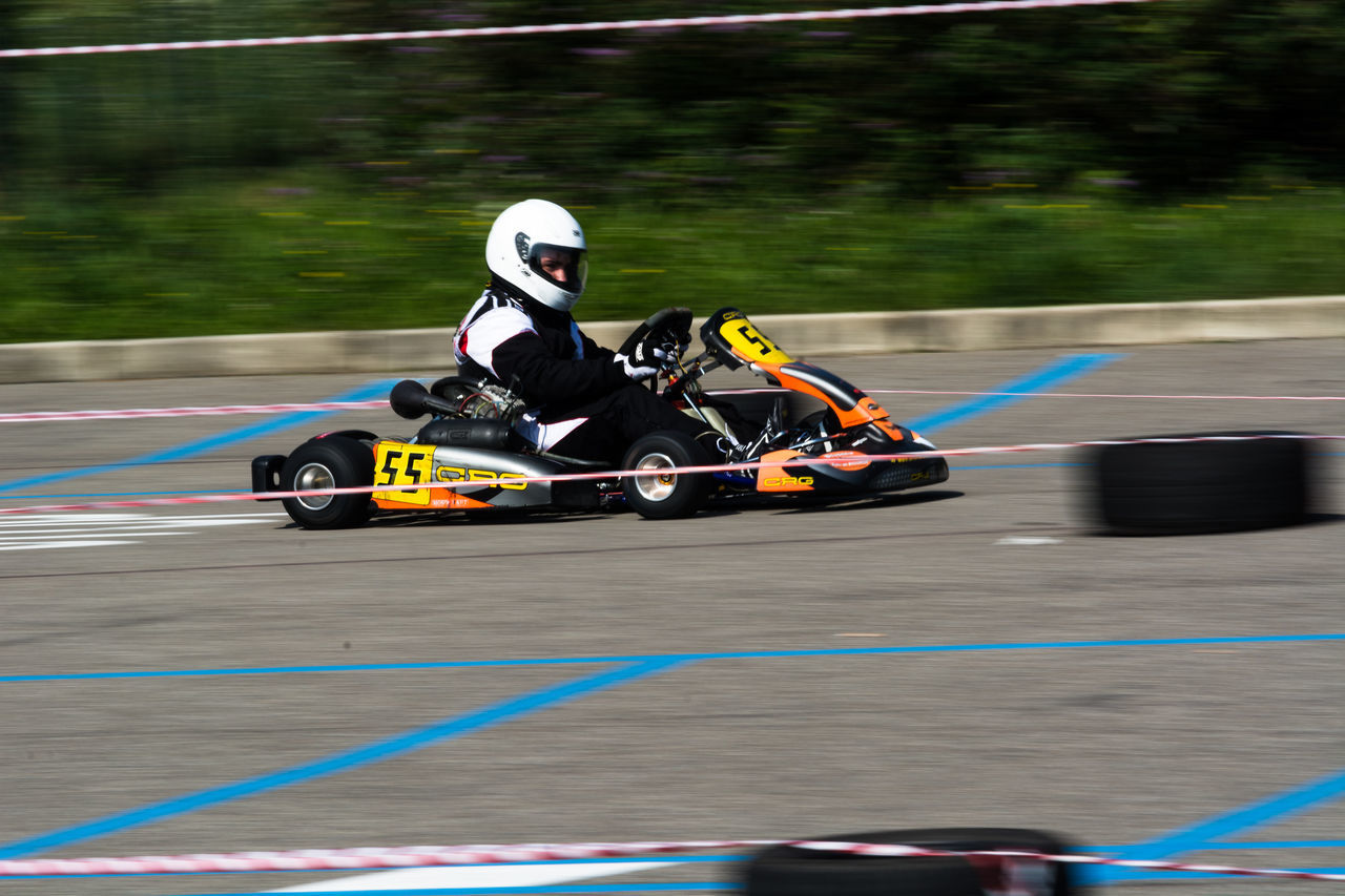 portrait of a go kart at a public event held in a parking lot Adults Only Auto Racing Competition Competitive Sport Crash Helmet Day Headwear Mode Of Transport Motor Racing Track Motorsport Outdoors People Professional Sport Racecar Speed Sport Sports Race Teamwork Two People