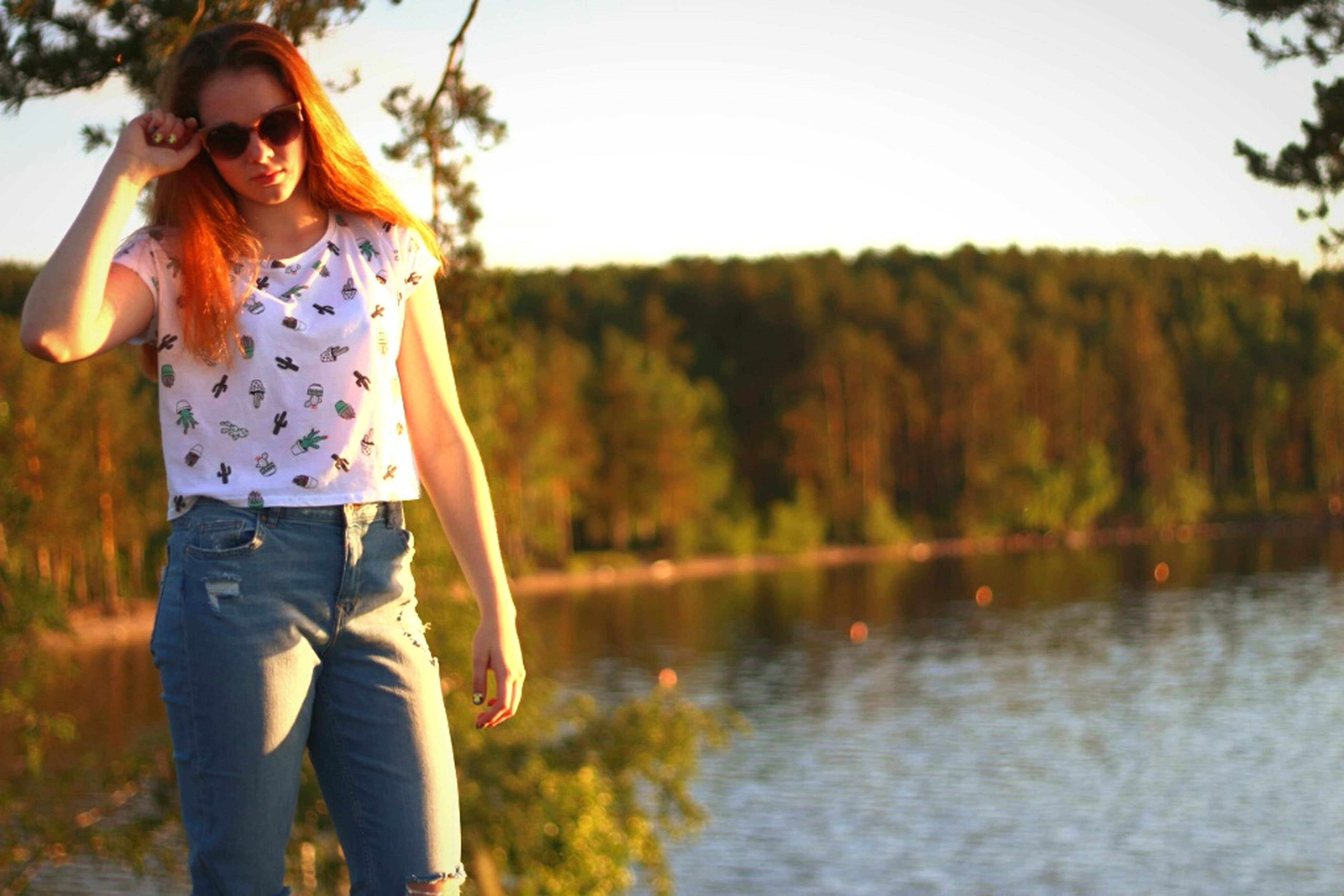 lake, water, tree, outdoors, casual clothing, nature, one person, reflection, leisure activity, day, long hair, focus on foreground, standing, young adult, one woman only, one young woman only, sunset, adult, only women, people, grass, full length, young women, beauty in nature, adults only, sky