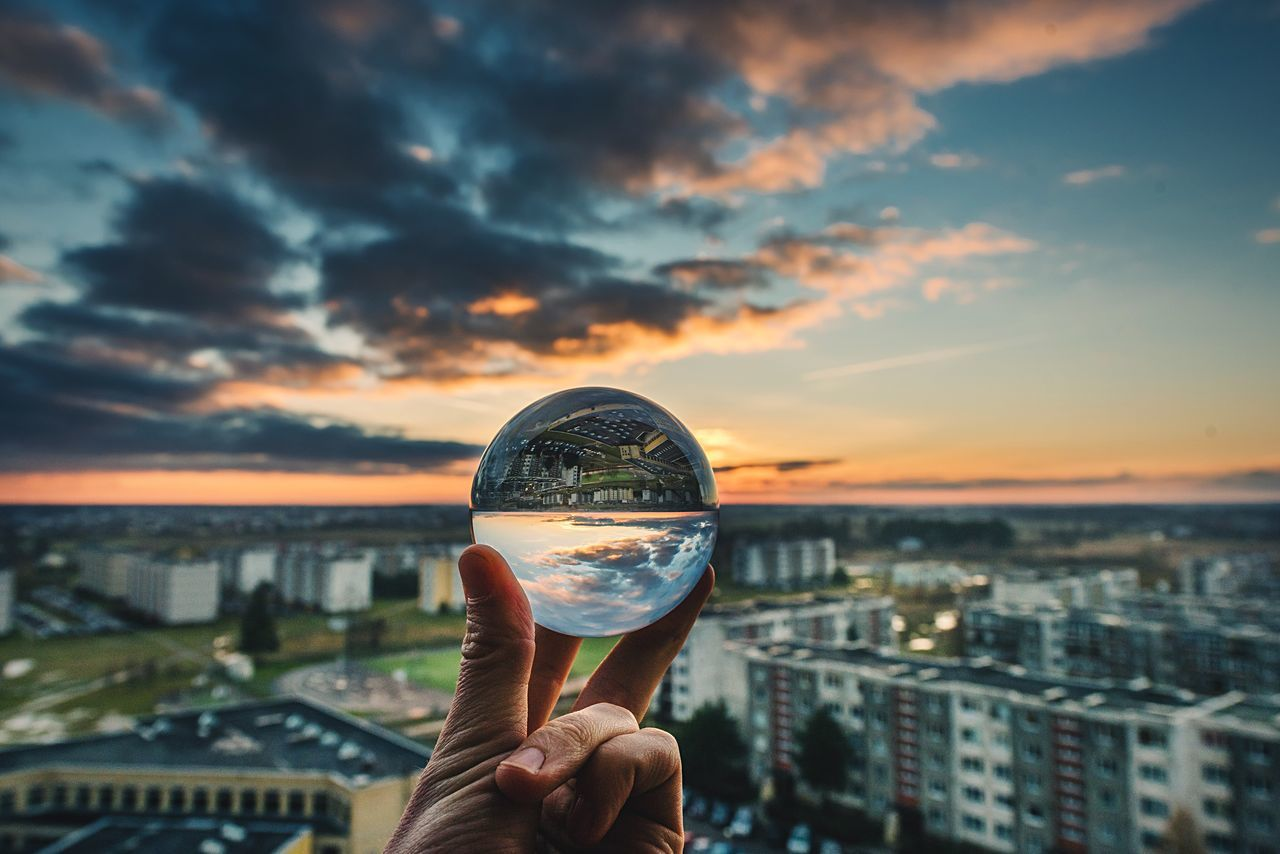 human hand, built structure, holding, sunset, architecture, sky, human body part, building exterior, human finger, focus on foreground, real people, cityscape, city, outdoors, cloud - sky, close-up, one person, nature, day, people