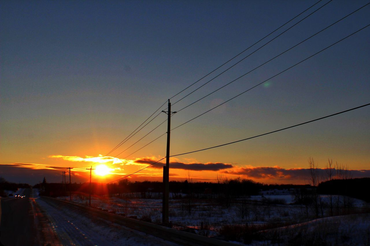 sunset, cable, rail transportation, sun, transportation, sky, connection, power line, nature, railroad track, no people, scenics, electricity pylon, outdoors, cold temperature, beauty in nature, winter, silhouette, tranquil scene, snow, tranquility, landscape, railway, clear sky, tree, day